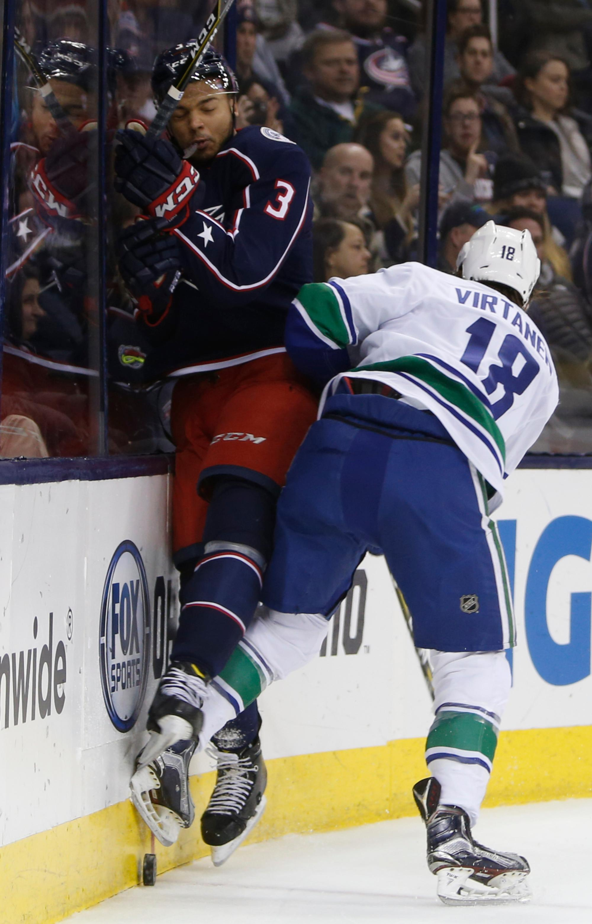 Vancouver Canucks' Jake Virtanen, right, checks Columbus Blue Jackets' Seth Jones during the first period of an NHL hockey game Friday, Jan. 12, 2018, in Columbus, Ohio. (AP Photo/Jay LaPrete)