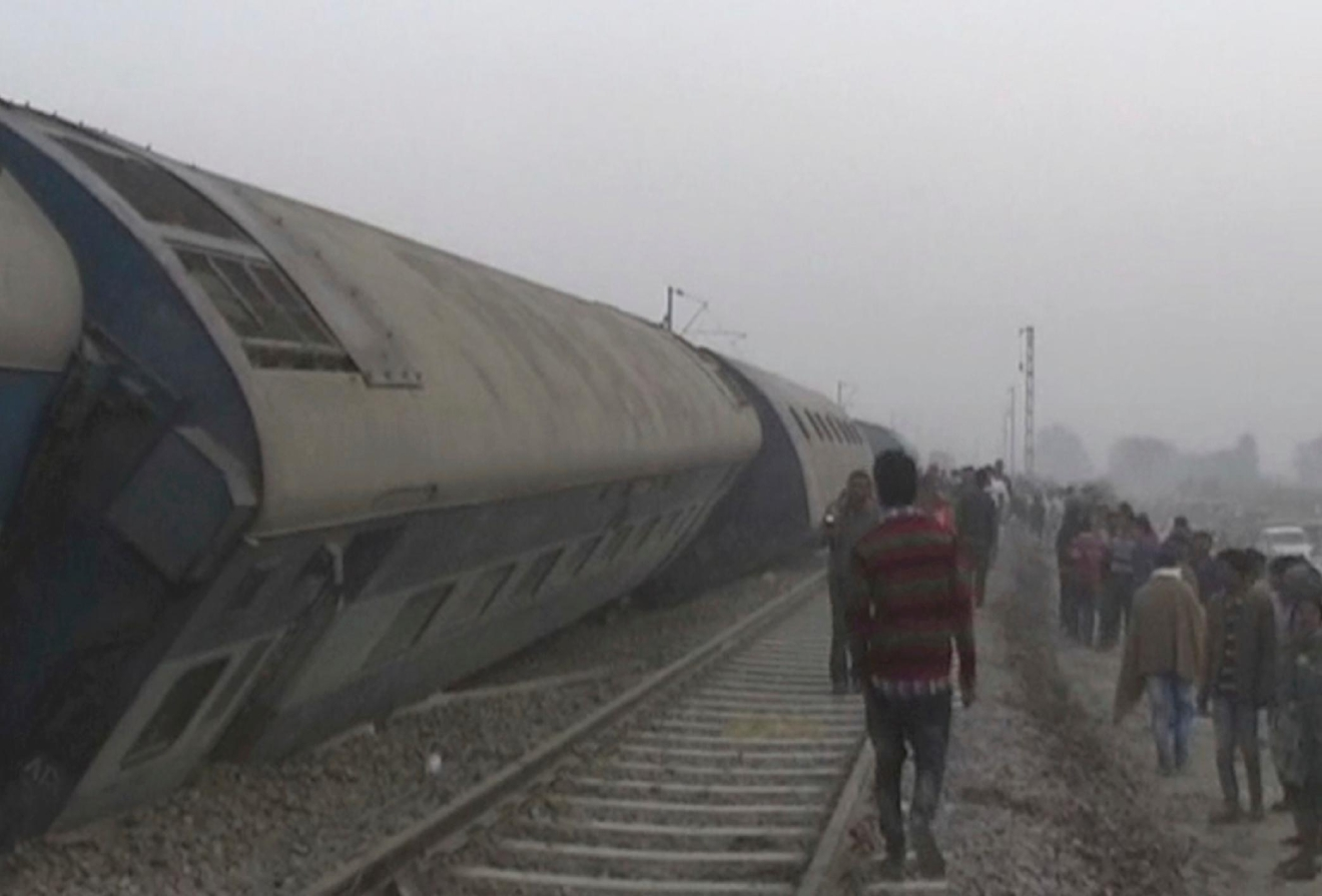 In this image made from video, people gather at the site of a train accident near Pukhrayan, about 270 kilometers (168 miles) from Allahabad, Sunday, Nov. 20, 2016. (KK Productions via AP)