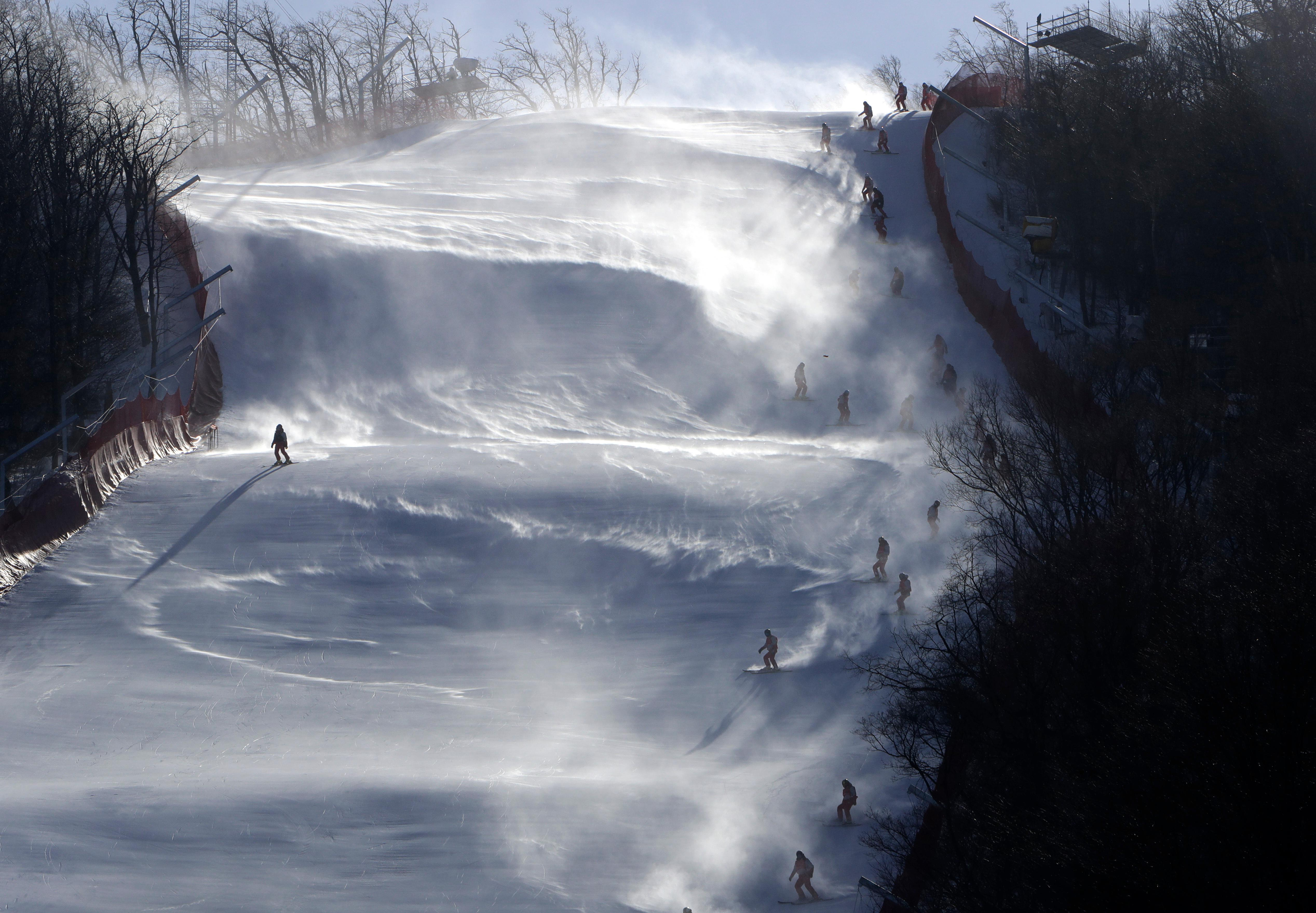 Course crew slide slip to the finish area after the women's giant slalom was postponed due to high winds at the 2018 Winter Olympics at the Yongpyong Alpine Center, Pyeongchang, South Korea, Monday, Feb. 12, 2018. (AP Photo/Michael Probst)