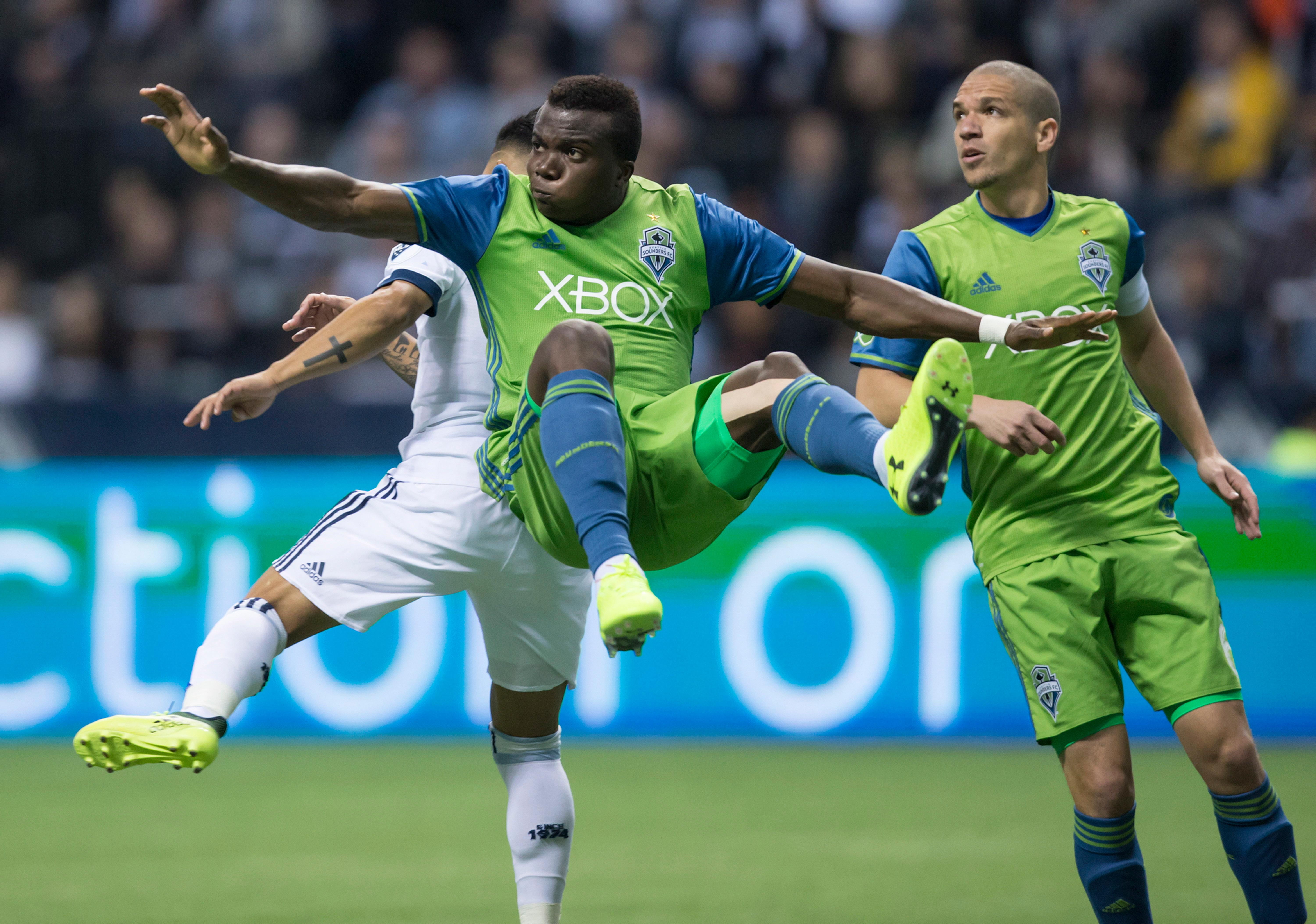 Seattle Sounders' Nouhou, front, of Cameroon, falls to the ground after kicking the ball away from Vancouver Whitecaps' Cristian Techera, back left, of Uruguay, as Seattle's Osvaldo Alonso, of Cuba, watches during the second half of an MLS playoff soccer match in Vancouver, British Columbia, Sunday, Oct. 29, 2017. (Darryl Dyck/The Canadian Press via AP)