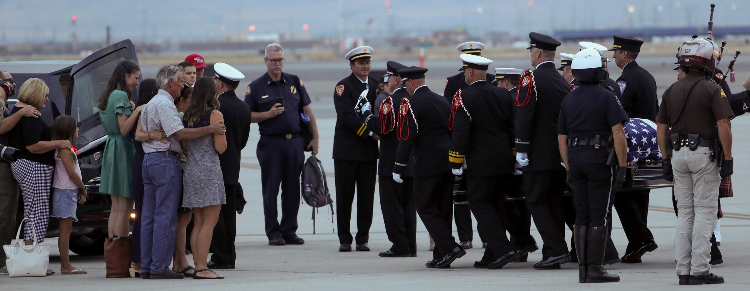 Members of the Draper City Fire Department and Unified Fire Authority Honor Guard carry the  casket of Draper Battalion Chief Matt Burchett to a hearse after being transported from California to Utah in a C130-J by the California Air National Guard. The C130-J landed at the Utah Air National Guard Base in Salt Lake City on Wednesday, Aug. 15, 2018. Burchett was killed while fighting the Mendocino Complex Fire north of San Francisco.