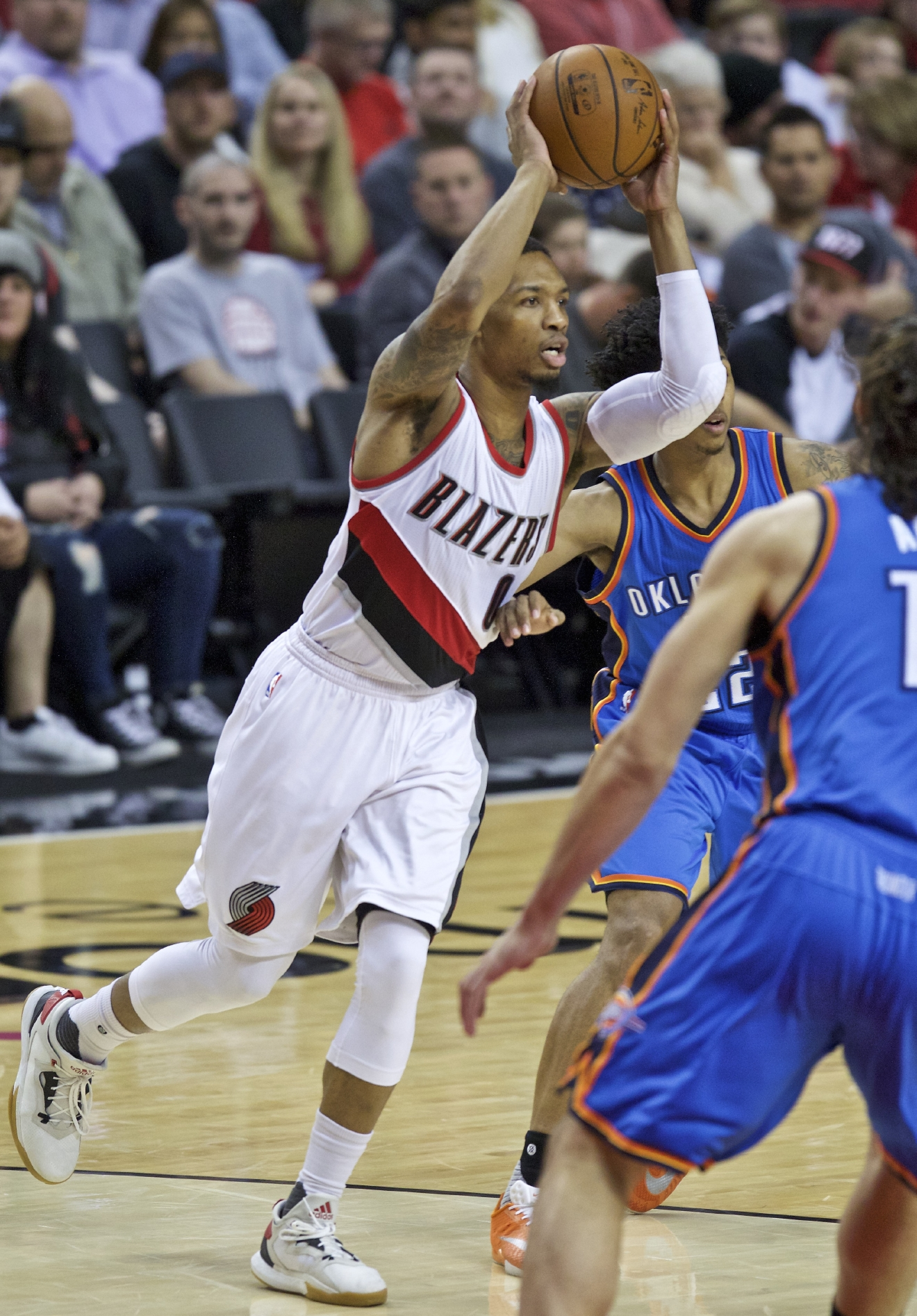 Portland Trail Blazers guard Damian Lillard, left, passes around Oklahoma City Thunder guard Cameron Payne, right, during the second half of an NBA basketball game in Portland, Ore., Wednesday, April 6, 2016. (AP Photo/Craig Mitchelldyer)