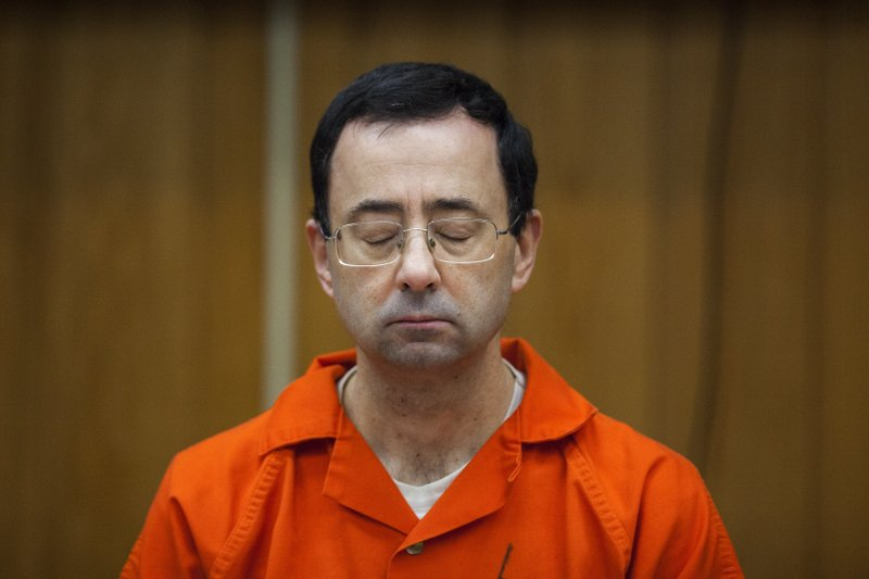 <p>Larry Nassar listens during his sentencing at Eaton County Circuit Court in Charlotte, Mich., Monday, Feb. 5, 2018. The former Michigan State University sports-medicine and USA Gymnastics doctor received 40 to 125 years for three first degree criminal sexual abuse charges related to assaults that occurred at Twistars, a gymnastics facility in Dimondale. Nassar has also been sentenced to 60 years in prison for three child pornography charges in federal court and between 40 to 175 years in Ingham County for seven counts of criminal sexual conduct. (Cory Morse /The Grand Rapids Press via AP</p>
