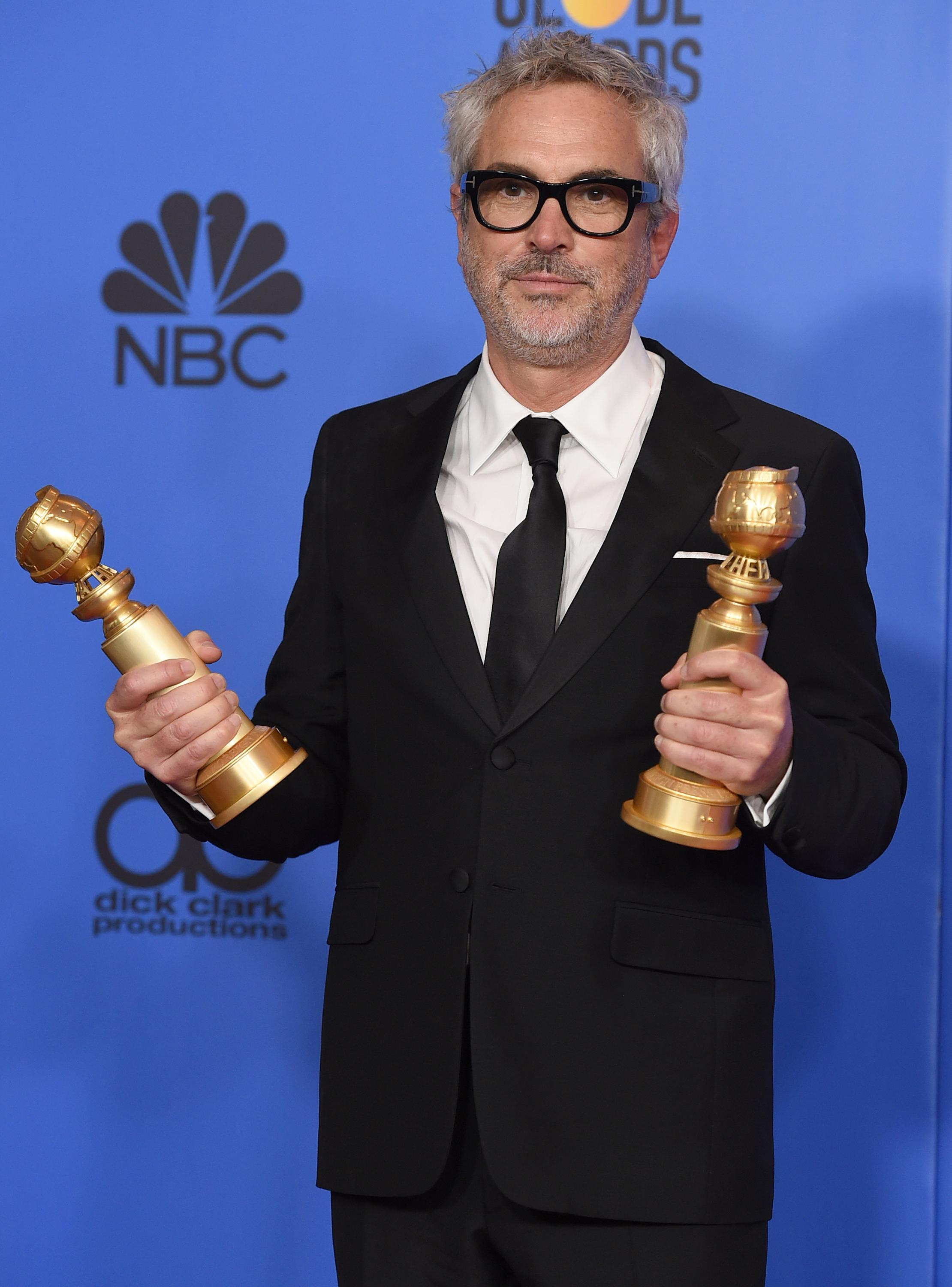 "Alfonso Cuaron poses in the press room with the awards for best director, motion picture and best motion picture, foreign language for ""Roma"" at the 76th annual Golden Globe Awards at the Beverly Hilton Hotel on Sunday, Jan. 6, 2019, in Beverly Hills, Calif. (Photo by Jordan Strauss/Invision/AP)"