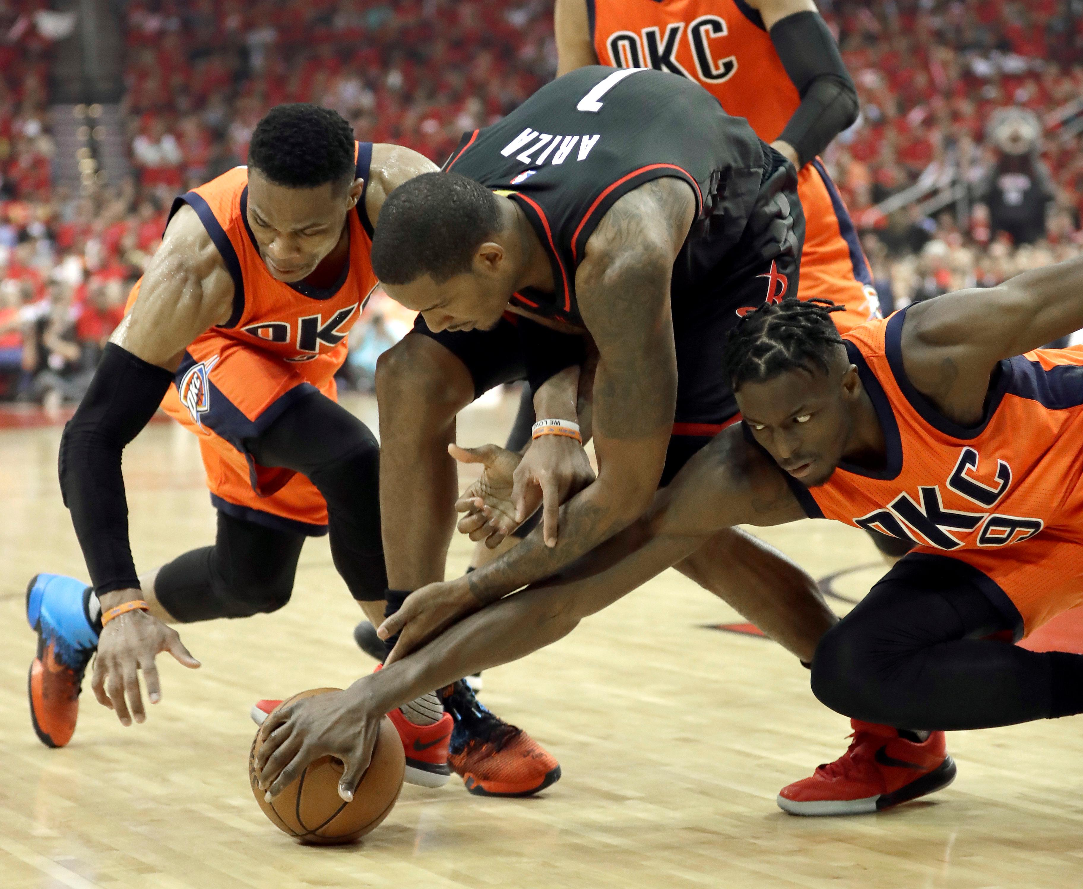 Houston Rockets' Trevor Ariza (1) battles Oklahoma City Thunder's Russell Westbrook, left, and Jerami Grant (9) for a loose ball during the second half in Game 1 of an NBA basketball first-round playoff series, Sunday, April 16, 2017, in Houston. (AP Photo/David J. Phillip)