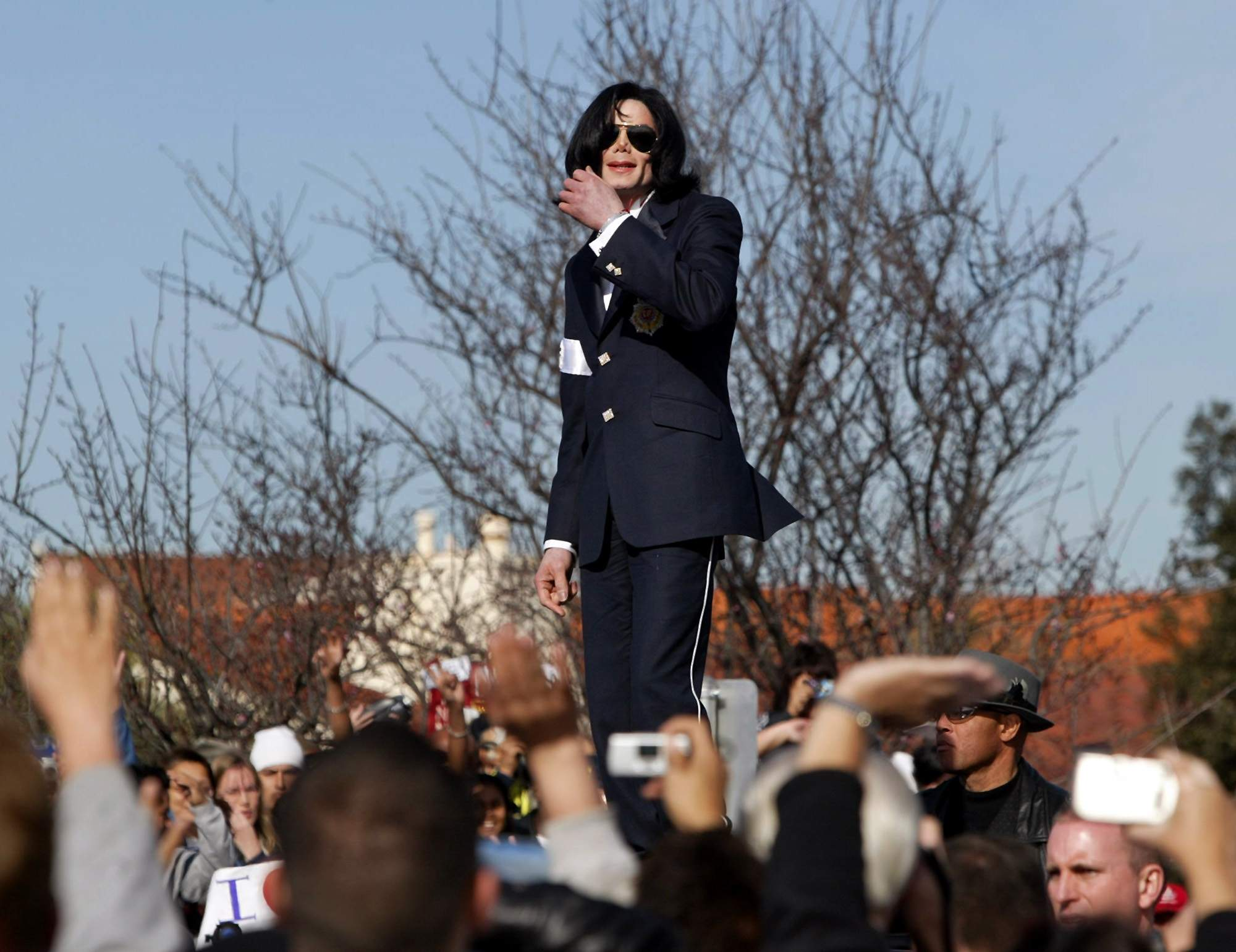 In this Friday, Jan. 16, 2004, file photo, Michael Jackson waves to his fans from atop his limousine after his arraignment on child molestation charges at the courthouse in Santa Maria, Calif. NICK UT/THE ASSOCIATED PRESS