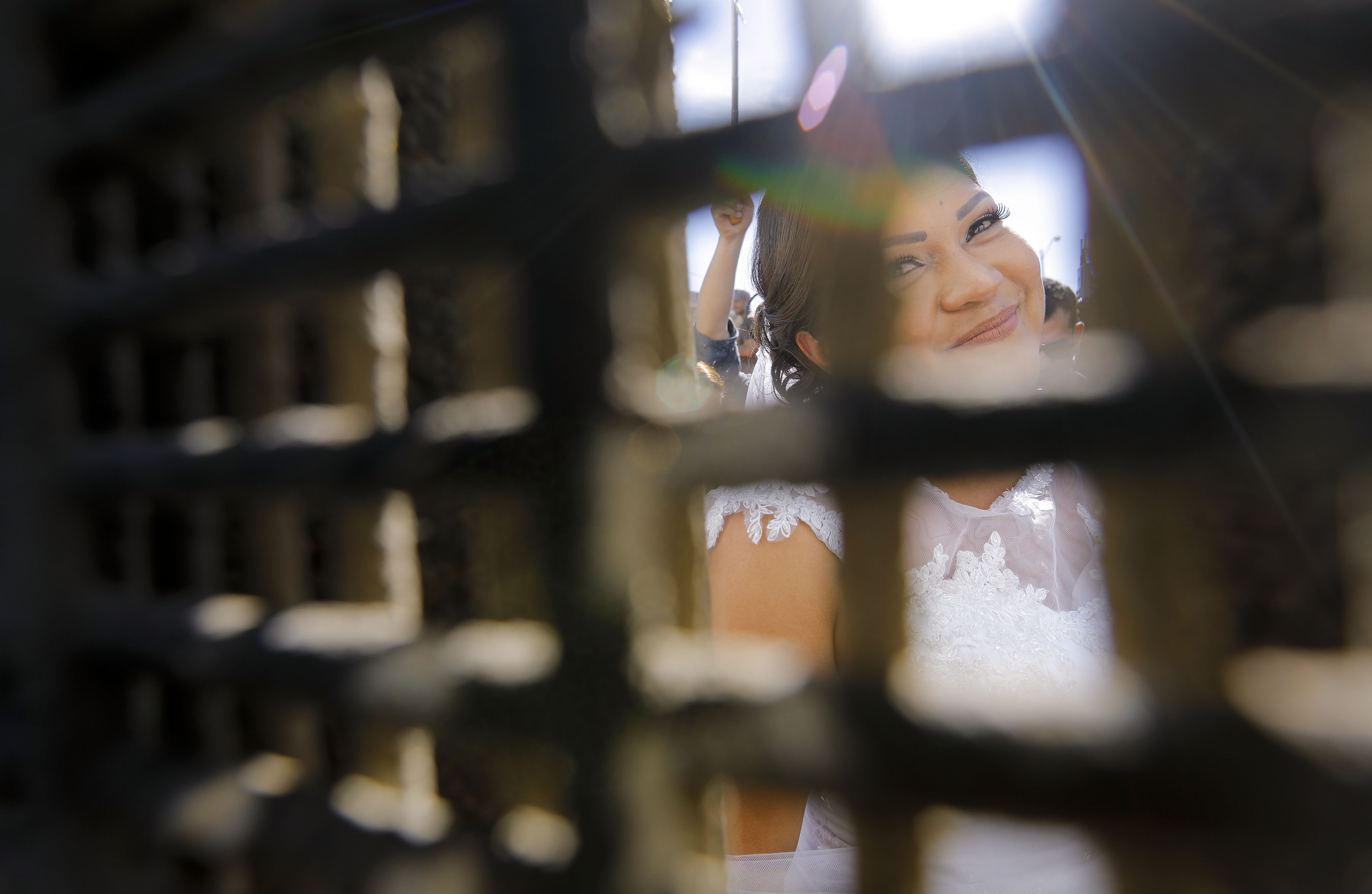 "In this Saturday, Nov. 18, 2017, photo, Evelia Reyes looks into the United States at Friendship Park, part of Border Field State Park, through the border fence from the Mexico side, before getting married to Brian Houston at the ""Door of Hope,"" part of the border fence between the U.S. and Mexico. The United States man and the Mexican woman wedded Saturday between the doors of a steel border gate that opens for only an hour or so every year. Their wedding in San Diego was the first for an opening of the gate known as the Door of Hope. (Howard Lipin//The San Diego Union-Tribune via AP)"