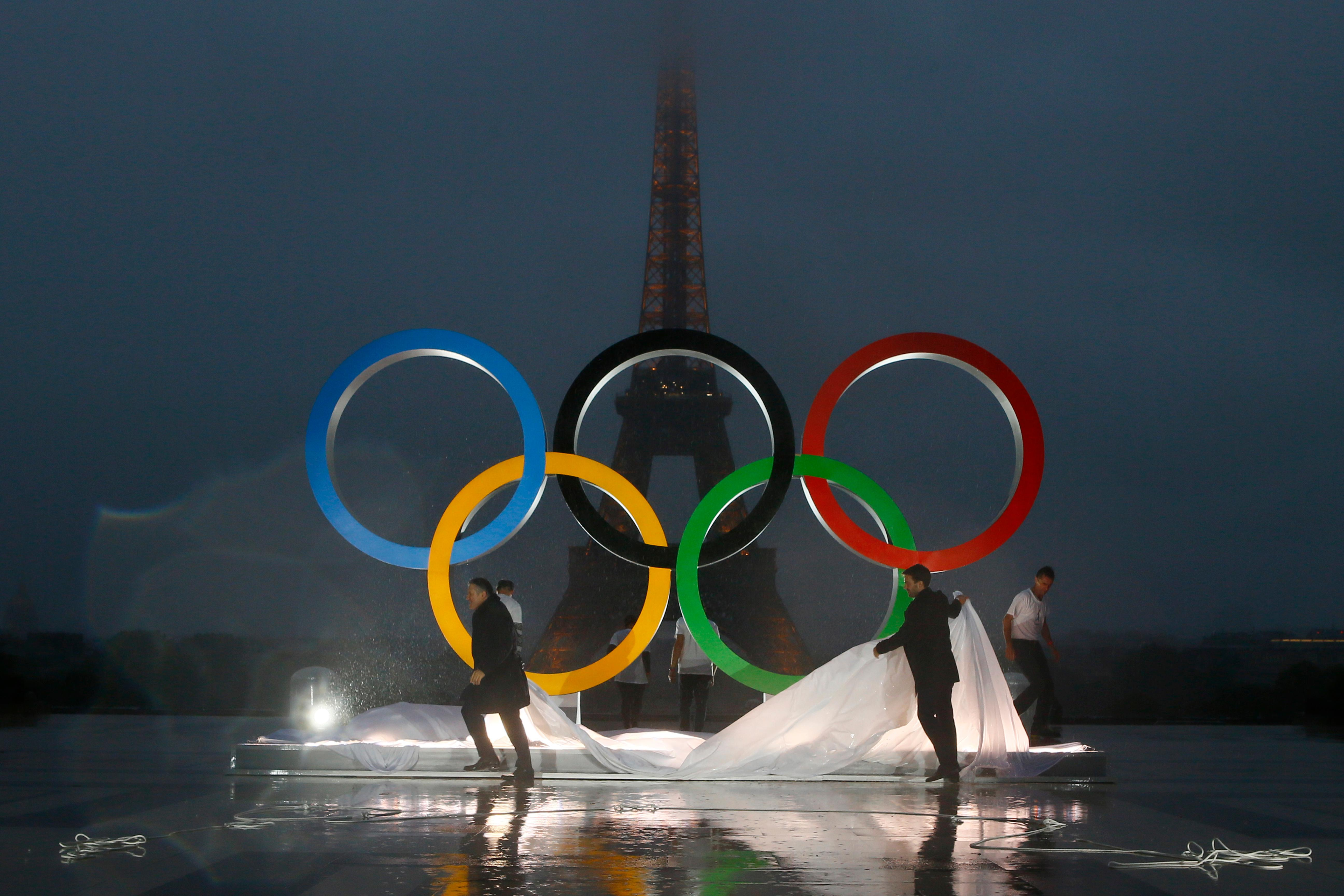 Paris officials unveil a display of the Olympic rings on Trocadero plaza that overlooks the Eiffel Tower, after the vote in Lima, Peru, awarding the 2024 Games to the French capital, in Paris, France, Wednesday, Sept. 13, 2017. Paris will host the 2024 Summer Olympics and Los Angeles will stage the 2028 Games — a pre-determined conclusion that the International Olympic Committee has officially ratified in a history-making vote. (AP Photo/Francois Mori)