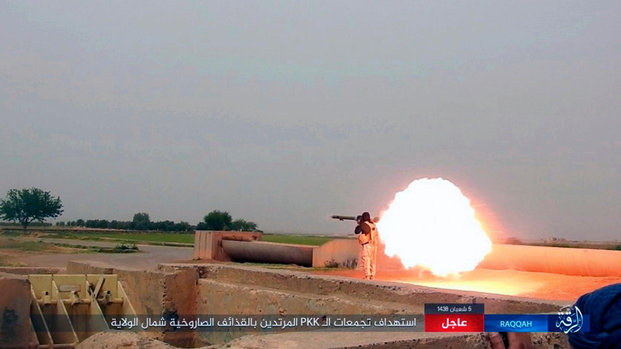 "This undated image posted online Monday, May. 1, 2017, by supporters of the Islamic State militant group on an anonymous photo sharing website, purports to show an Islamic State fighter firing his weapon during clashes with  U.S.-backed Kurdish-led Syrian Democratic Forces, in the northern Syrian province of Raqqa. The Britain-based Syrian Observatory for Human Rights and Kurdish activists said Tuesday, May 2, 2017, that a surprise attack in northeastern Syria carried out by IS has killed over 20 people, including displaced civilians. Arabic banner reads, ""Targeting gatherings of the infidel PKK  with rockets north of the province."" (Militant Photo via AP)"