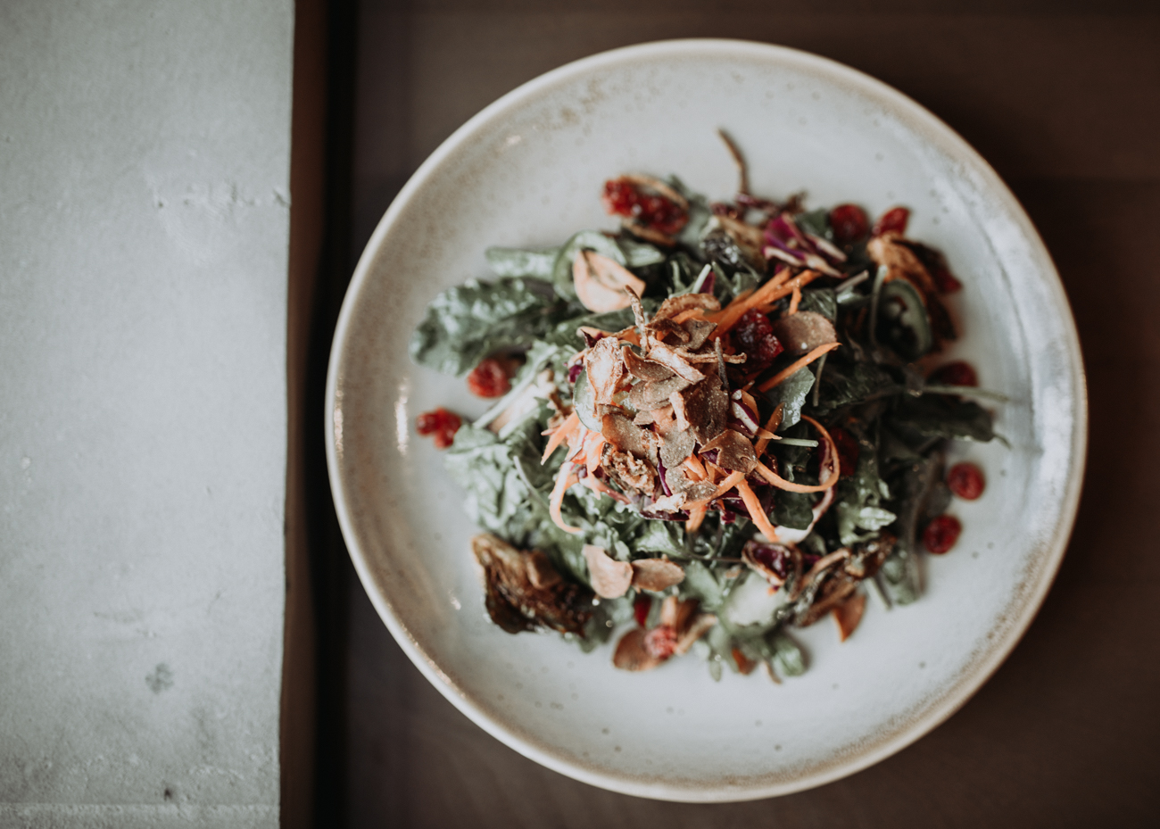 Kale and brussels sprouts salad with marinated cabbage, carrots, jalapenos, dried cranberries, and crispy shallots tossed in a sweet chili ginger vinaigrette / Image: Brianna Long // Published: 5.17.18