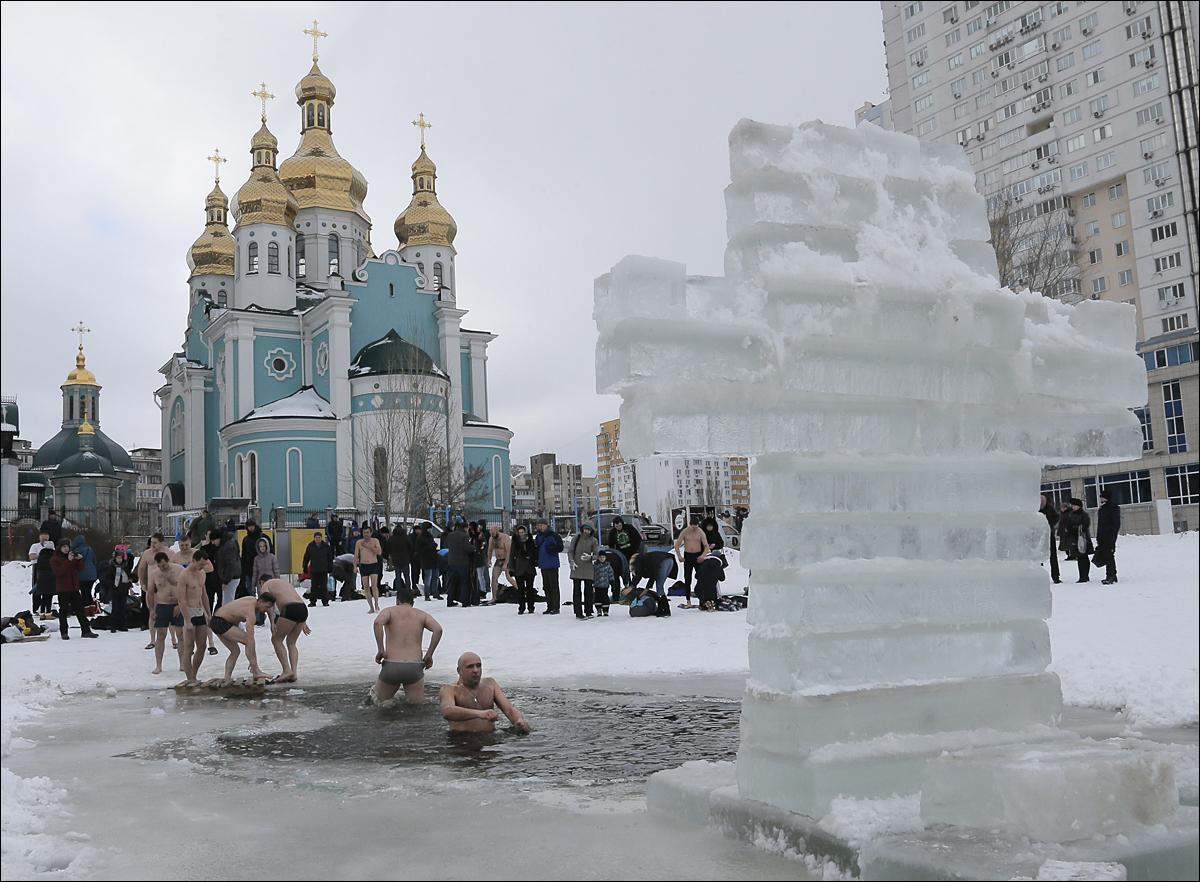 Orthodox believers plunge in icy water during the celebration of the Epiphany in Kiev, Ukraine, Tuesday, Jan. 19, 2016. Thousands of Orthodox believers celebrate the holiday of the Epiphany on Jan. 19, and traditionally plunge into holes cut through thick ice on rivers and ponds to cleanse themselves with water deemed holy for the day. (AP Photo/Efrem Lukatsky)