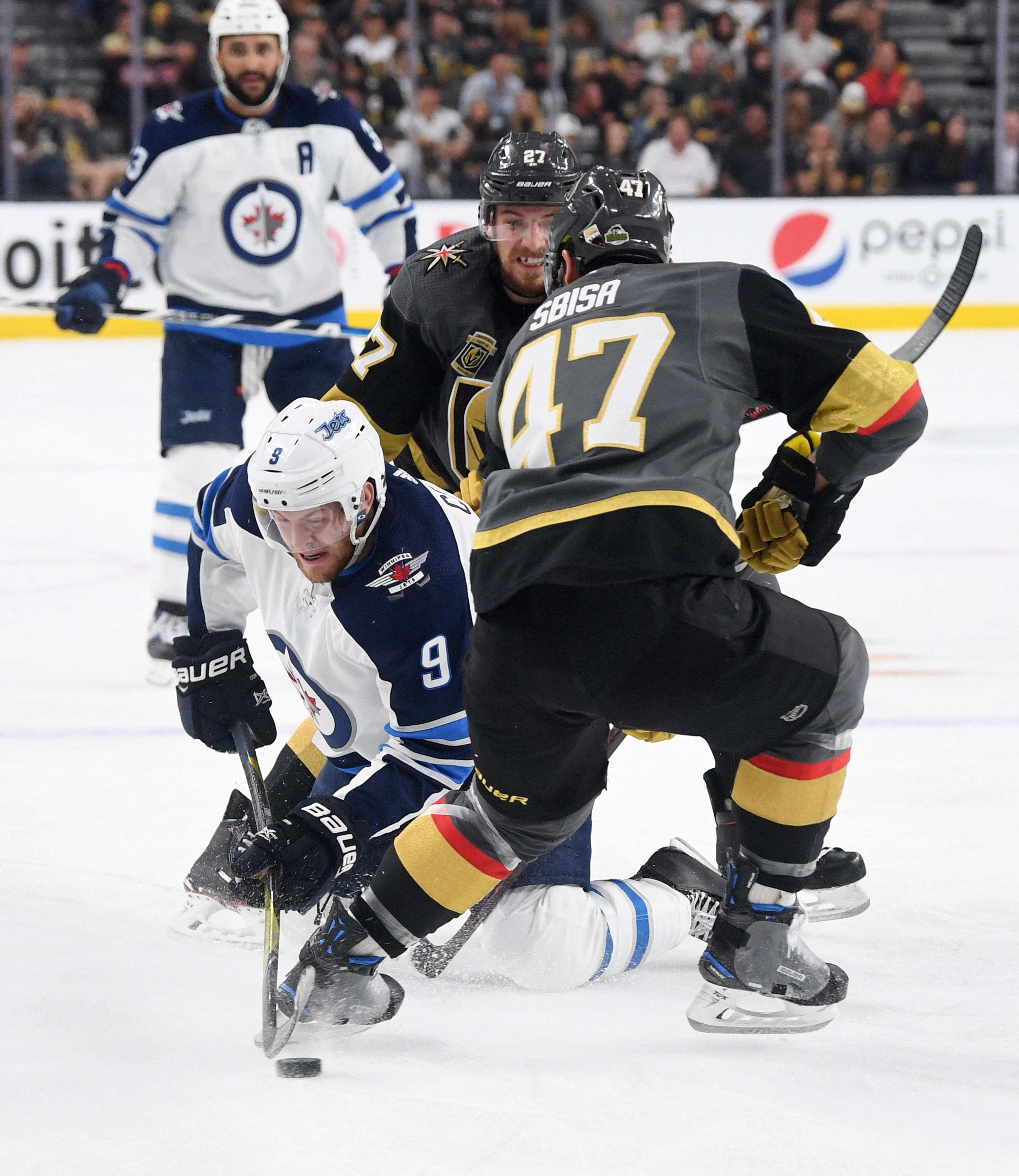 Winnipeg Jets center Andrew Copp (9) falls to the ice while trying to get a pass off around Vegas Golden Knights defenseman Luca Sbisa (47) during Game 3 of their NHL hockey Western Conference Final game Wednesday, May 16, 2018, at T-Mobile Arena. CREDIT: Sam Morris/Las Vegas News Bureau