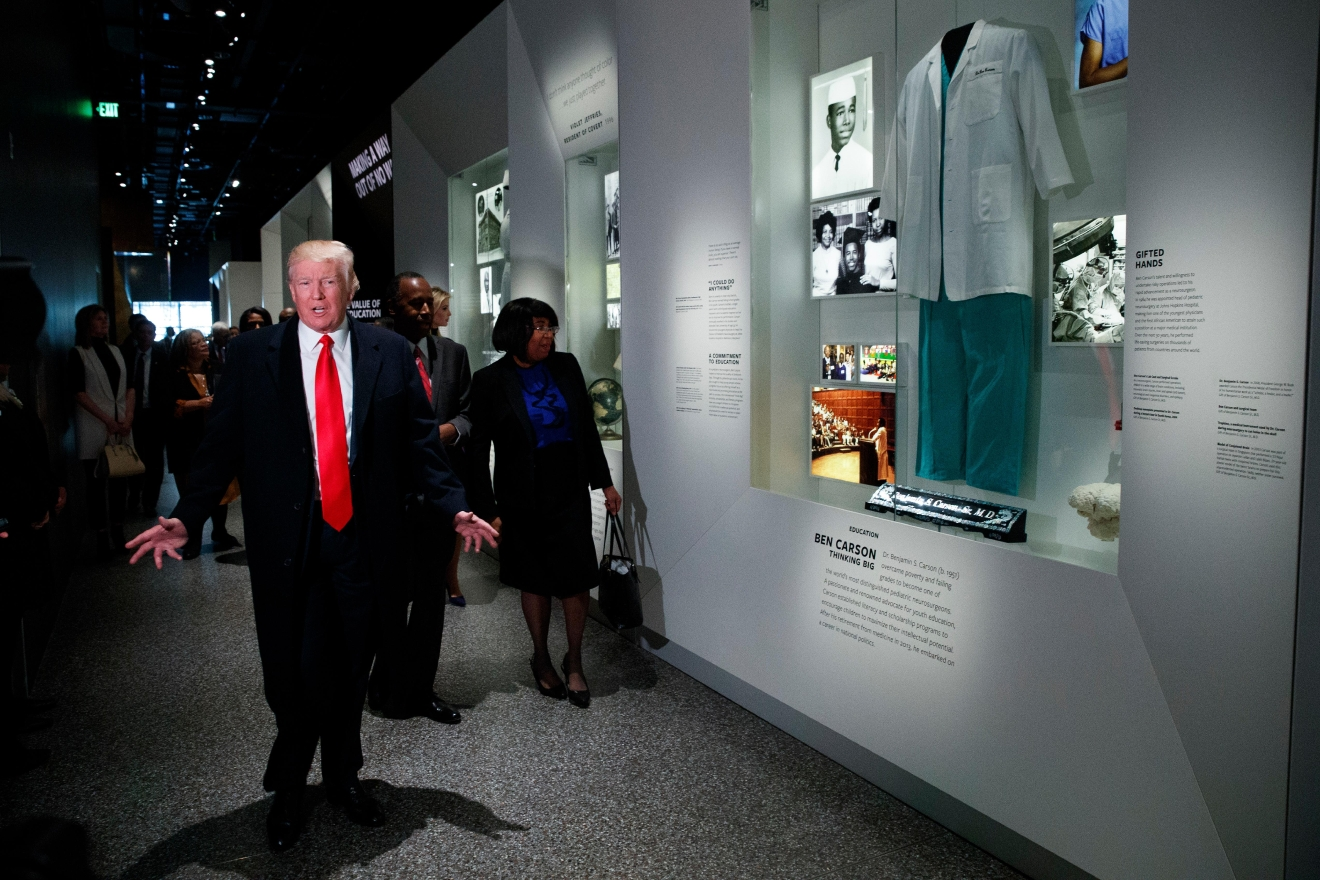 President Donald Trump walks past an exhibit for Dr. Ben Carson, his nominee for Housing and Urban Development secretary, during a tour of the National Museum of African American History and Culture, Tuesday, Feb. 21, 2017, in Washington. (AP Photo/Evan Vucci)