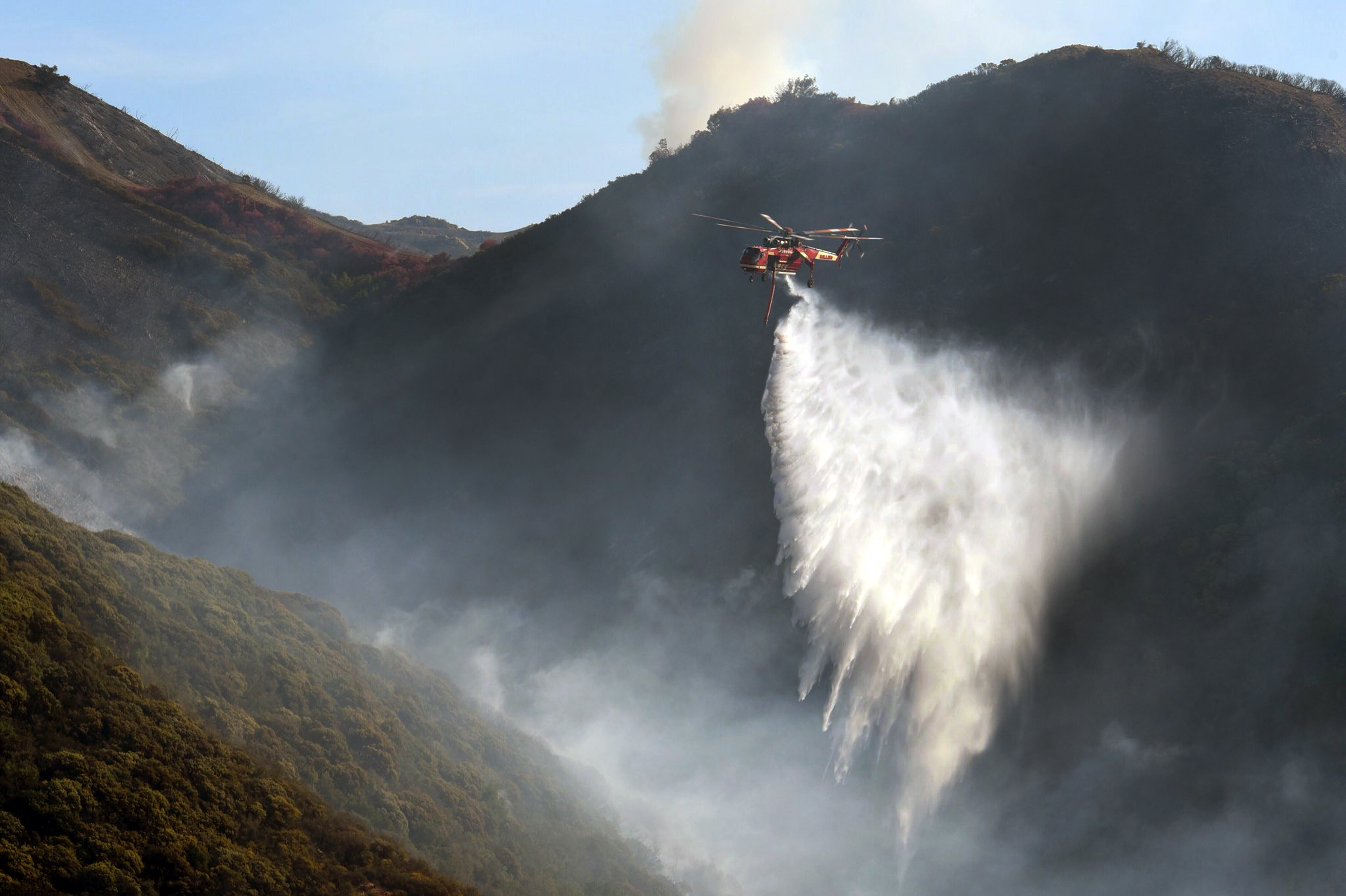 In this photo provided by the Santa Barbara County Fire Department, a Sikorsky S-64 Skycrane makes a water drop on hot spots along the hillside east of Gibraltar Road in Santa Barbara, Calif., Sunday morning, Dec. 17, 2017. One of the largest wildfires in California history is now 40 percent contained but flames still threaten coastal communities as dry, gusty winds are predicted to continue.(Mike Eliason/Santa Barbara County Fire Department via AP)