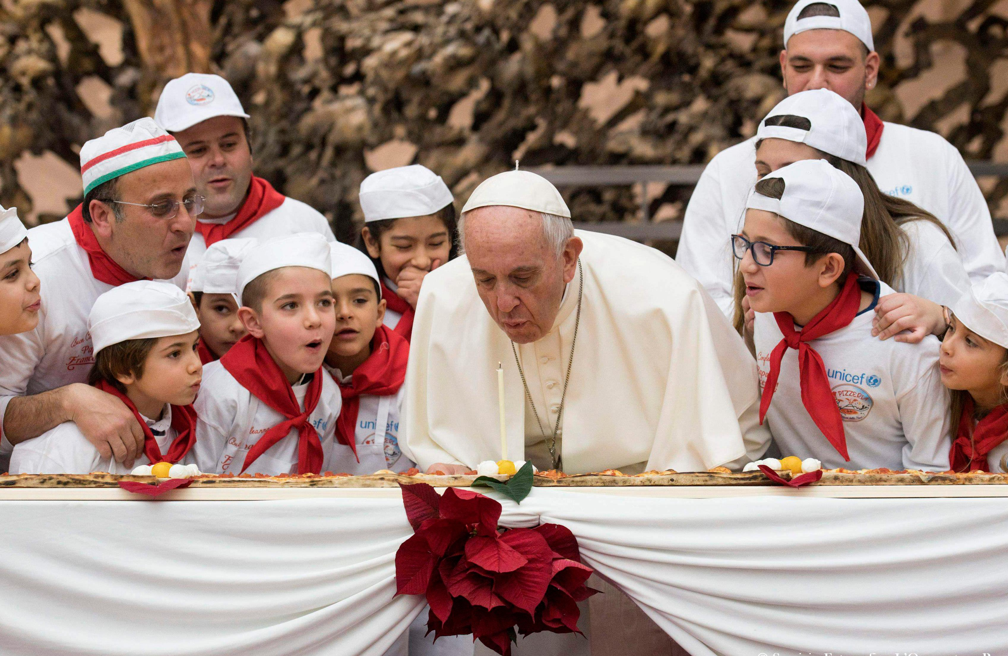 Pope Francis blows a candle on the occasion of his 81st birthday during a private audience with children the Paul VI hall at the Vatican, Sunday, Dec. 17, 2017. (L'Osservatore Romano/Pool Photo via AP)