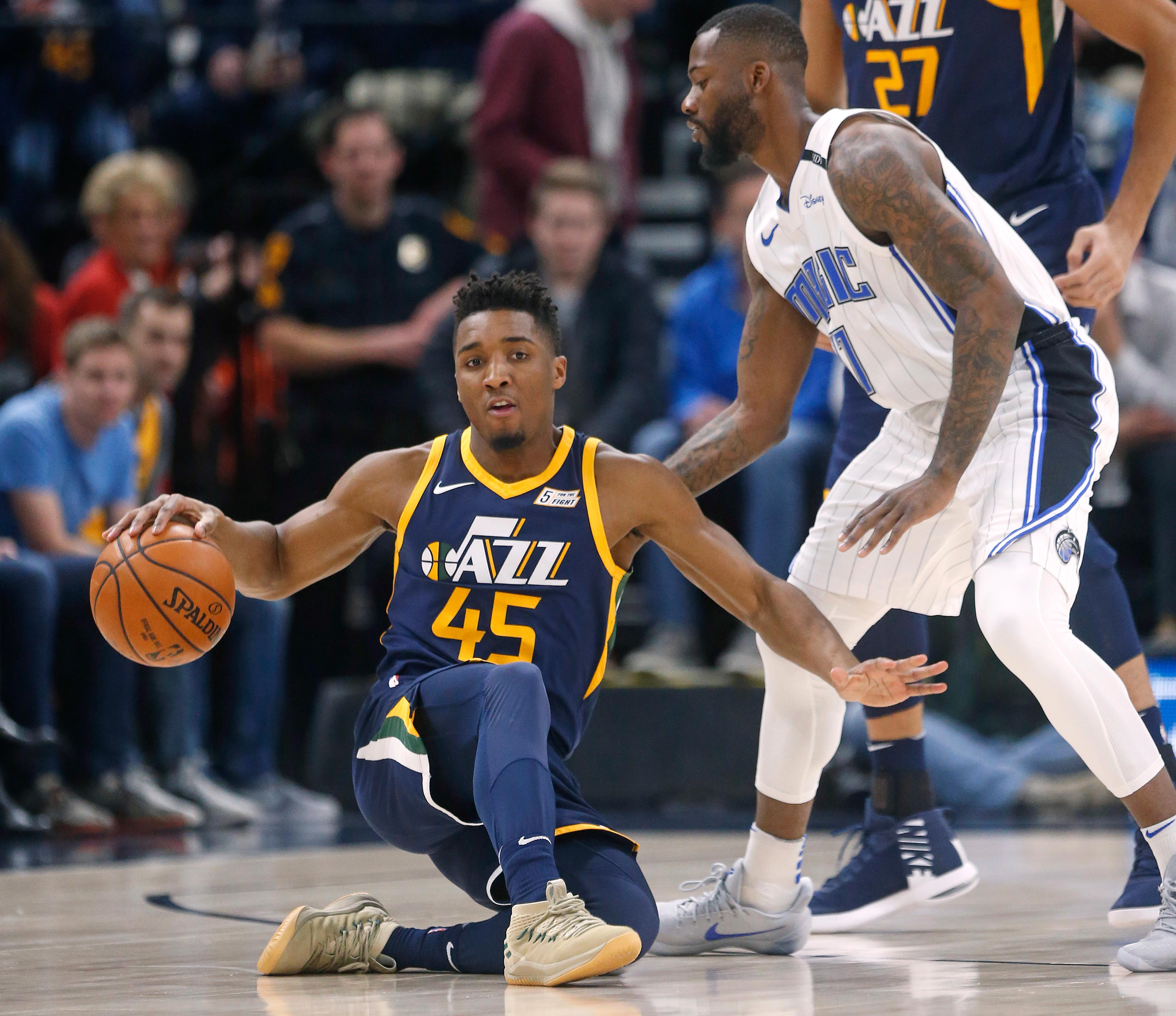 Orlando Magic forward Jonathon Simmons, right, guards against Utah Jazz guard Donovan Mitchell (45) in the first half during an NBA basketball game Monday, March 5, 2018, in Salt Lake City. (AP Photo/Rick Bowmer)