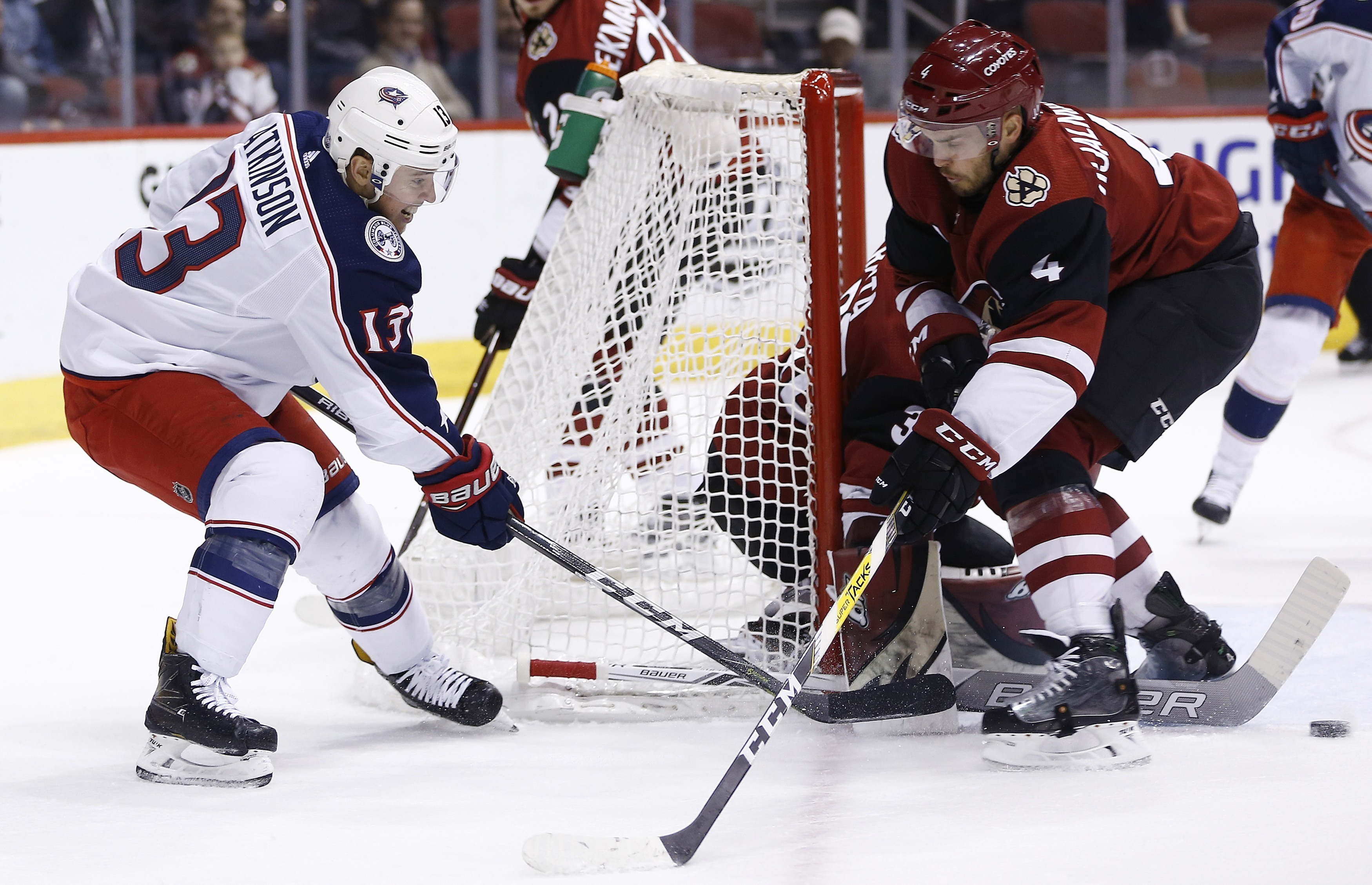 Columbus Blue Jackets right wing Cam Atkinson (13) passes the puck past Arizona Coyotes defenseman Niklas Hjalmarsson (4) during the first period of an NHL hockey game, Thursday, Jan. 25, 2018, in Glendale, Ariz. (AP Photo/Ross D. Franklin)