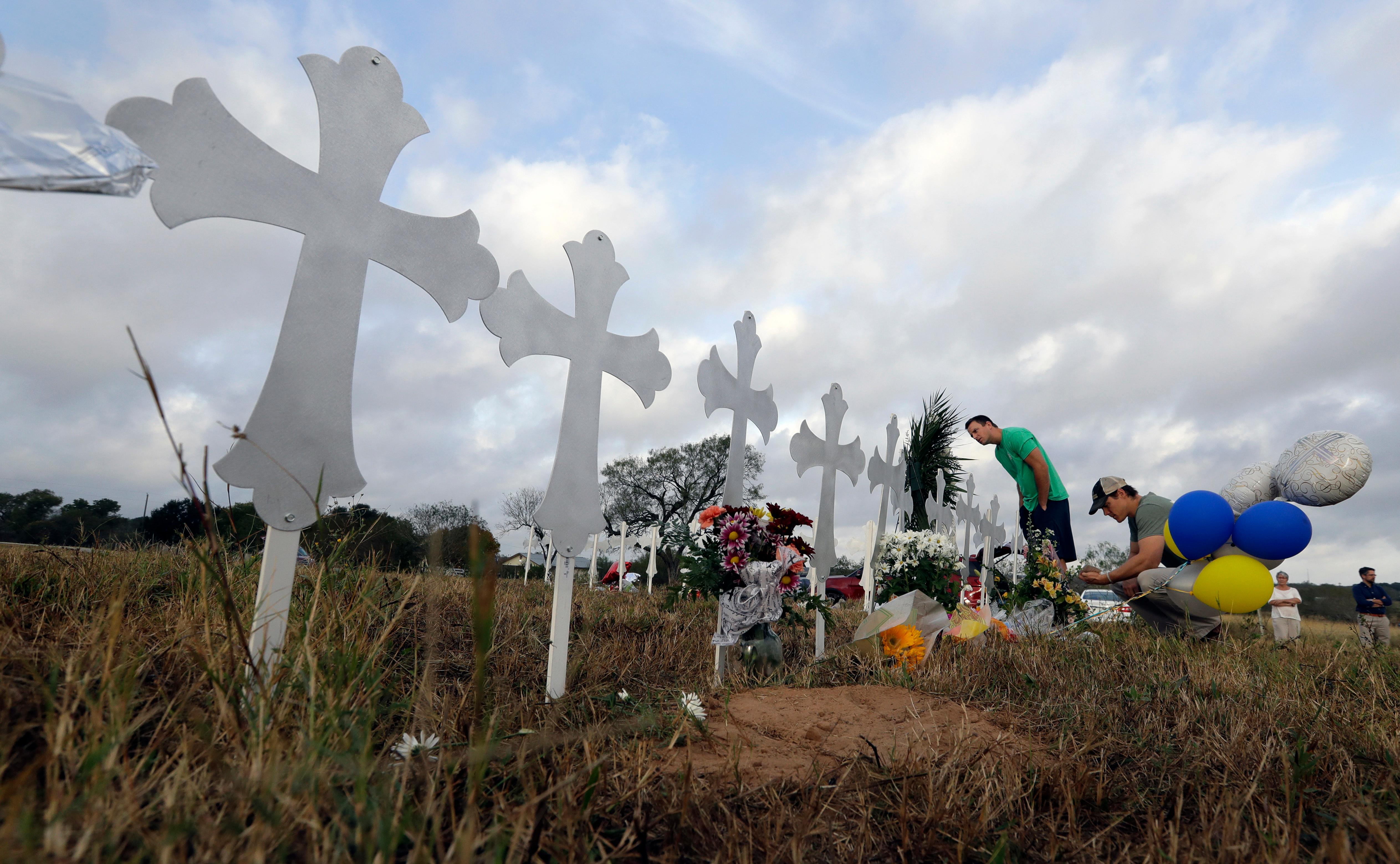 Kevin Blomstrum, left, and Kyle Dahlberg visit a makeshift memorial for victims near the scene of a shooting at the First Baptist Church of Sutherland Springs, Tuesday, Nov. 7, 2017, in Sutherland Springs, Texas. A man opened fire inside the church in the small South Texas community on Sunday, killing more than two dozen and injuring others. (AP Photo/Eric Gay)