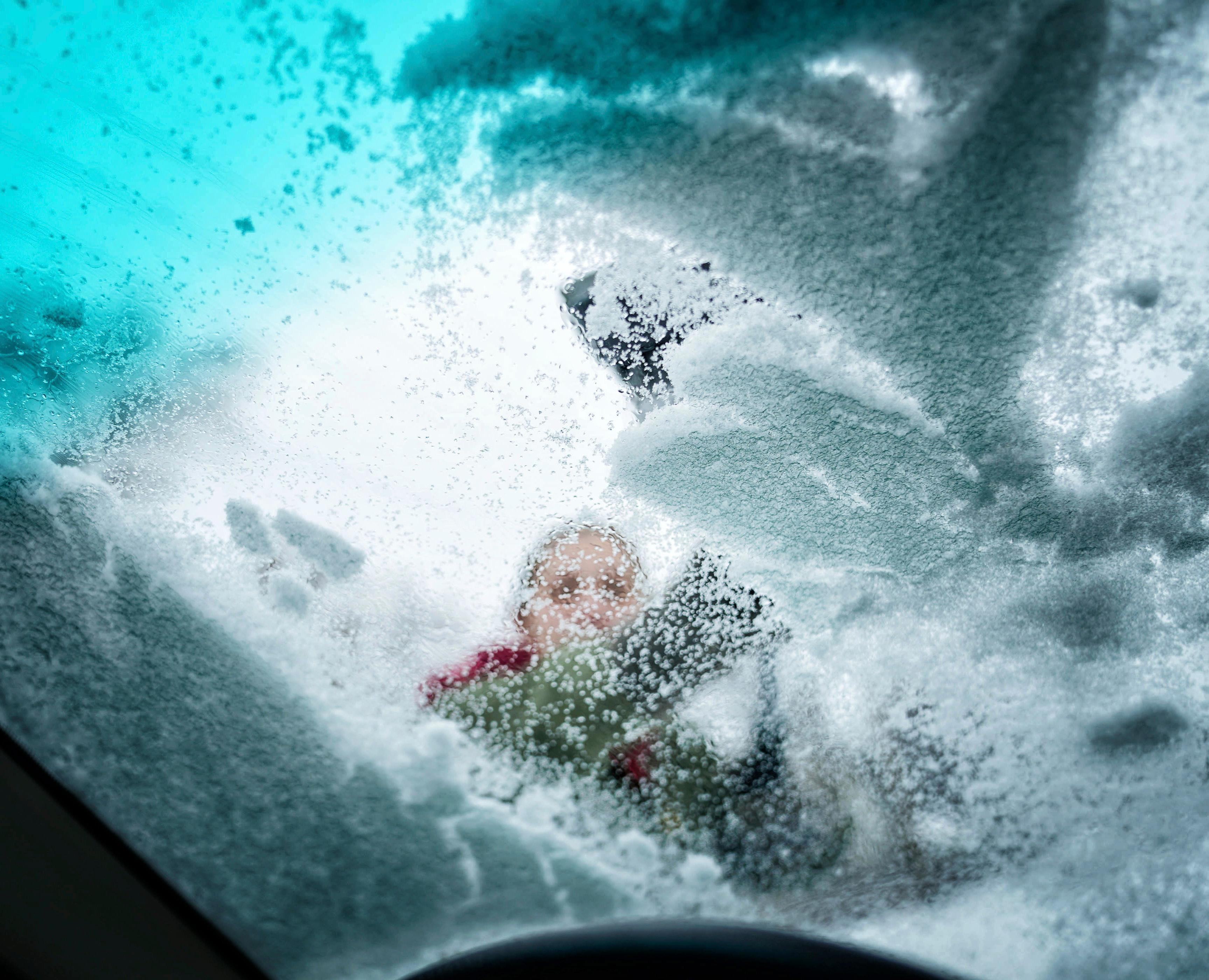 Claire Radtke cleaned the sloppy wet snow from her windshield Tuesday, April 3, 2018,  before heading out to do some errands in St. Paul, Minn. (Glen Stubbe/Star Tribune via AP)