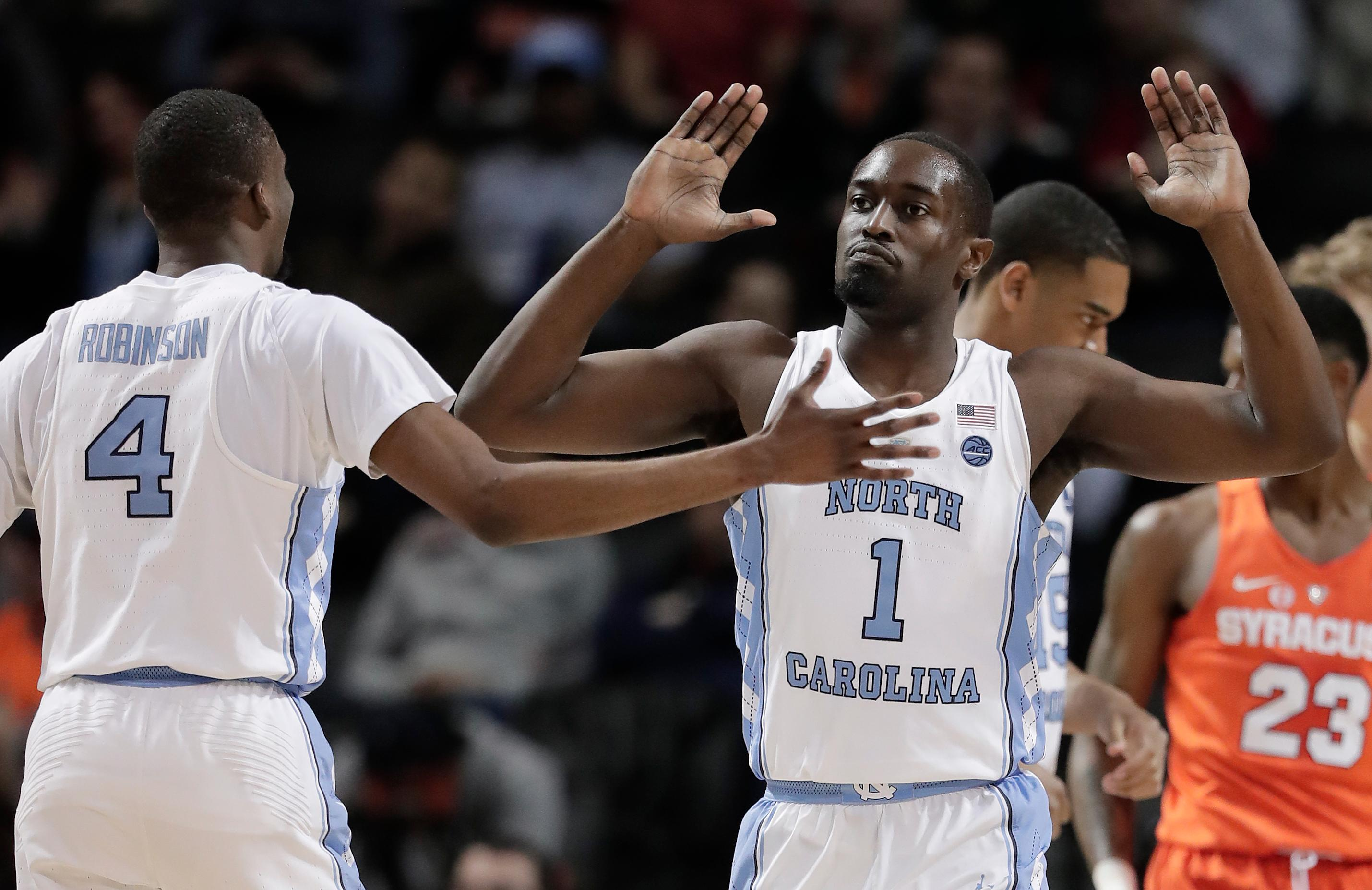 North Carolina forward Theo Pinson (1) high-fives guard Brandon Robinson (4) after scoring against Syracuse during the first half of an NCAA college basketball game in the second round of the Atlantic Coast Conference men's tournament Wednesday, March 7, 2018, in New York. (AP Photo/Julie Jacobson)