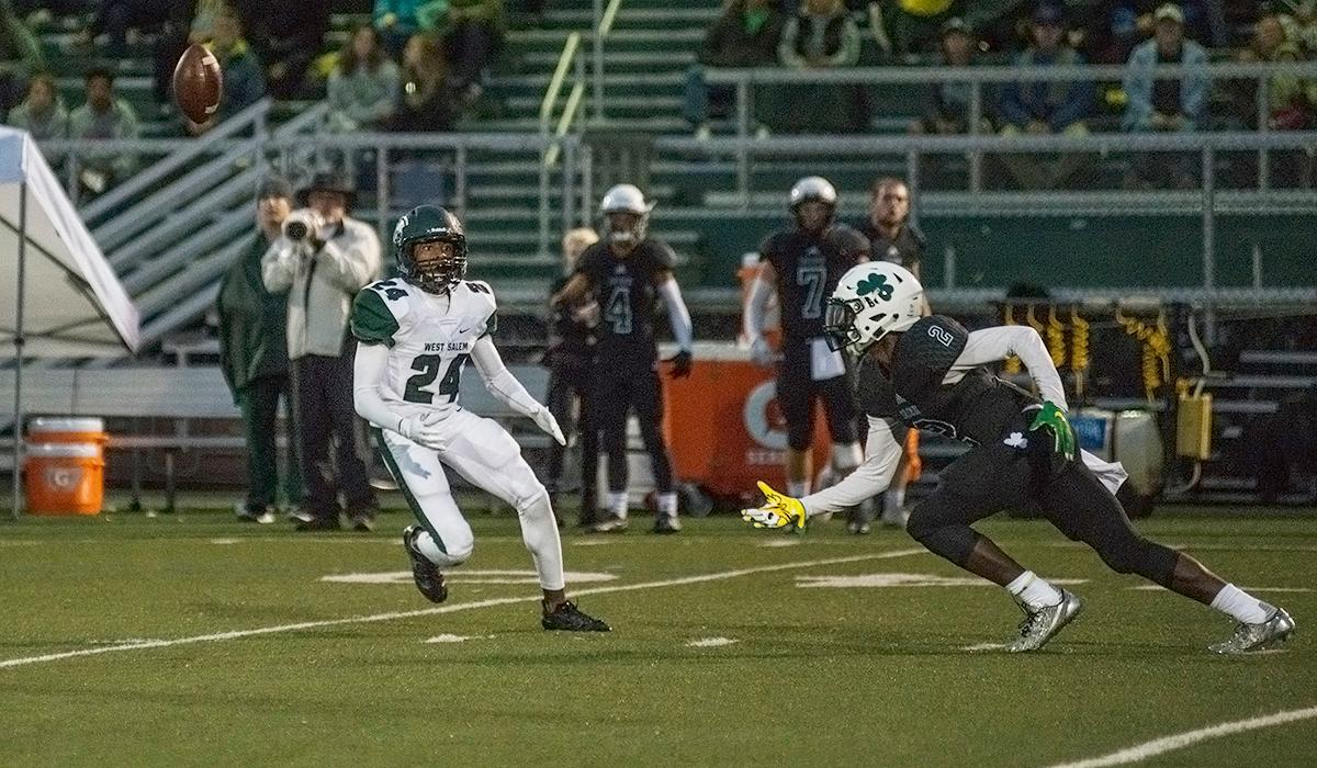 Sheldon Irish wide receiver Raymond Woodie (#2) goes for the ball as West Salem Titans wide receiver Jamal McMurrin (#24) approaches.  On a rainy Monday evening, Sheldon defeated West Salem 41 to 7 at their home field. The game had been postponed from Friday due to unhealthy levels of smoke in the atmosphere from nearby forest fires. Abigail Winn, Oregon News Lab