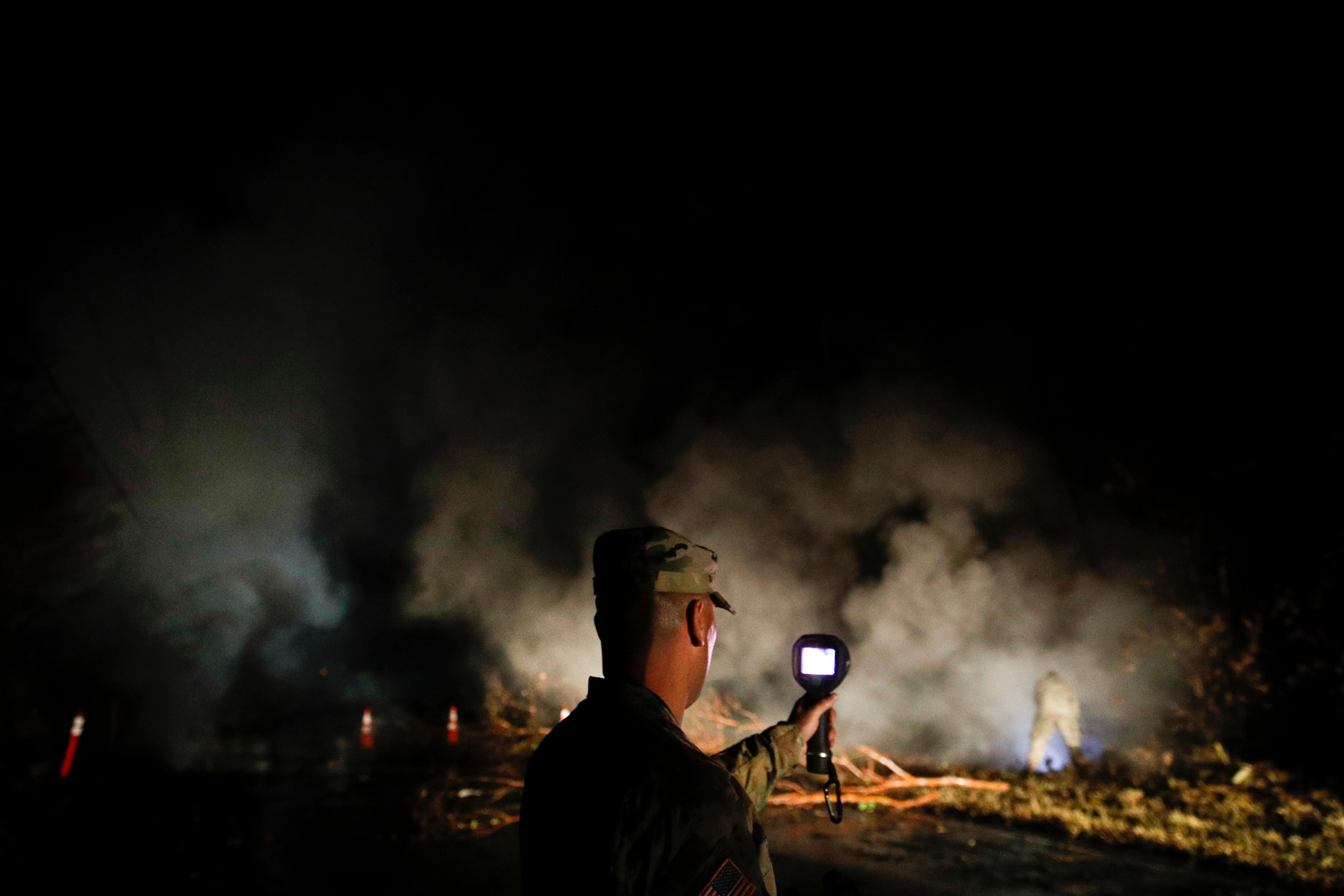 First Lt. Aaron Hew Len, and Sgt. 1st Class Carl Satterwaite, background right, of the U.S. National Guard, test air quality near cracks emitting volcanic gases from a lava flow in the Leilani Estates subdivision near Pahoa, Hawaii on Thursday, May 10, 2018. Kilauea has destroyed more than 35 structures since it began releasing lava from vents about 25 miles (40 kilometers) east of the summit crater. (AP Photo/Jae C. Hong)