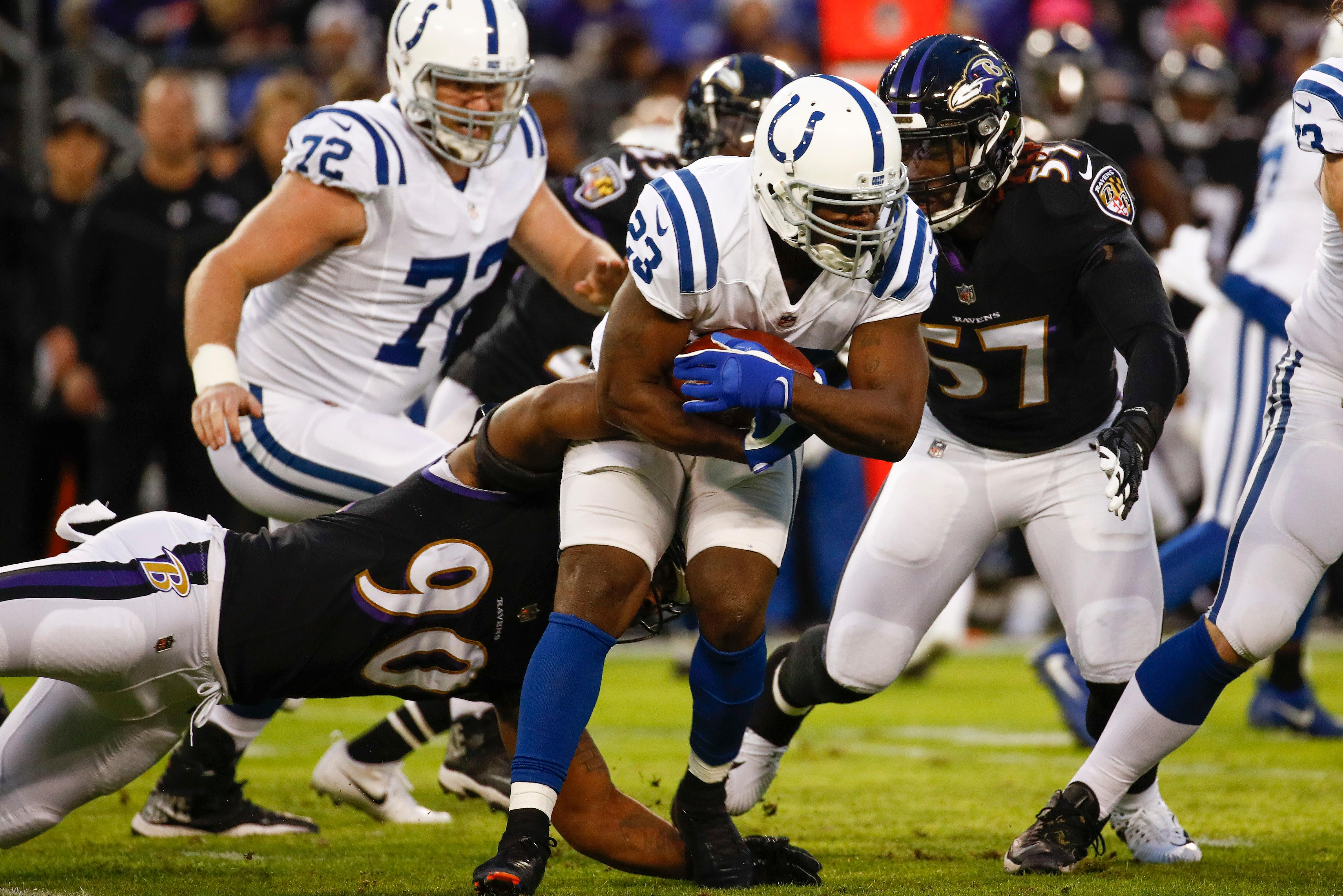 Indianapolis Colts running back Frank Gore (23) is stopped by Baltimore Ravens defensive end Za'Darius Smith (90) and inside linebacker C.J. Mosley (57) during the first half of an NFL football game in Baltimore, Saturday, Dec 23, 2017. (AP Photo/Patrick Semansky)