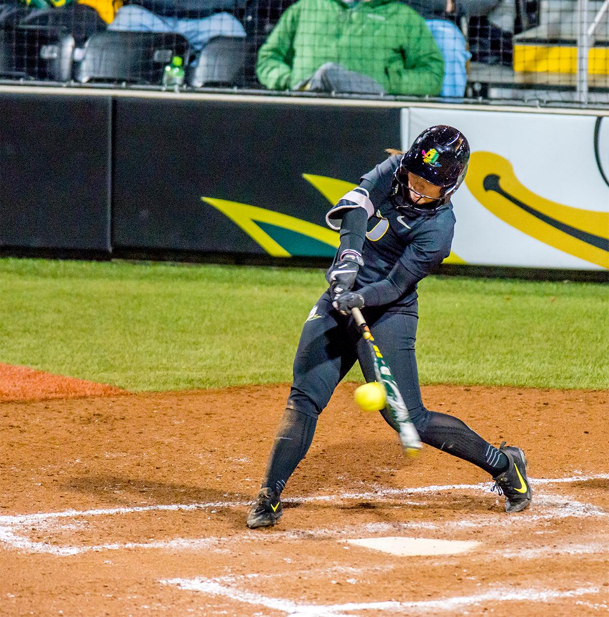 The Duck's Nikki Udria (#3) connects with the ball. In Game Two of a three-game series, the University of Oregon Ducks softball team defeated the University of Washington Huskies 4-1 Friday night in Jane Sanders Stadium. Danica Mercado (#2), Alexis Mack (#10) and Mia Camuso (#7) all scored in the win, Mack twice. The Ducks play the Huskies for the tie breaker on Saturday with the first pitch at noon. Photo by August Frank, Oregon News Lab