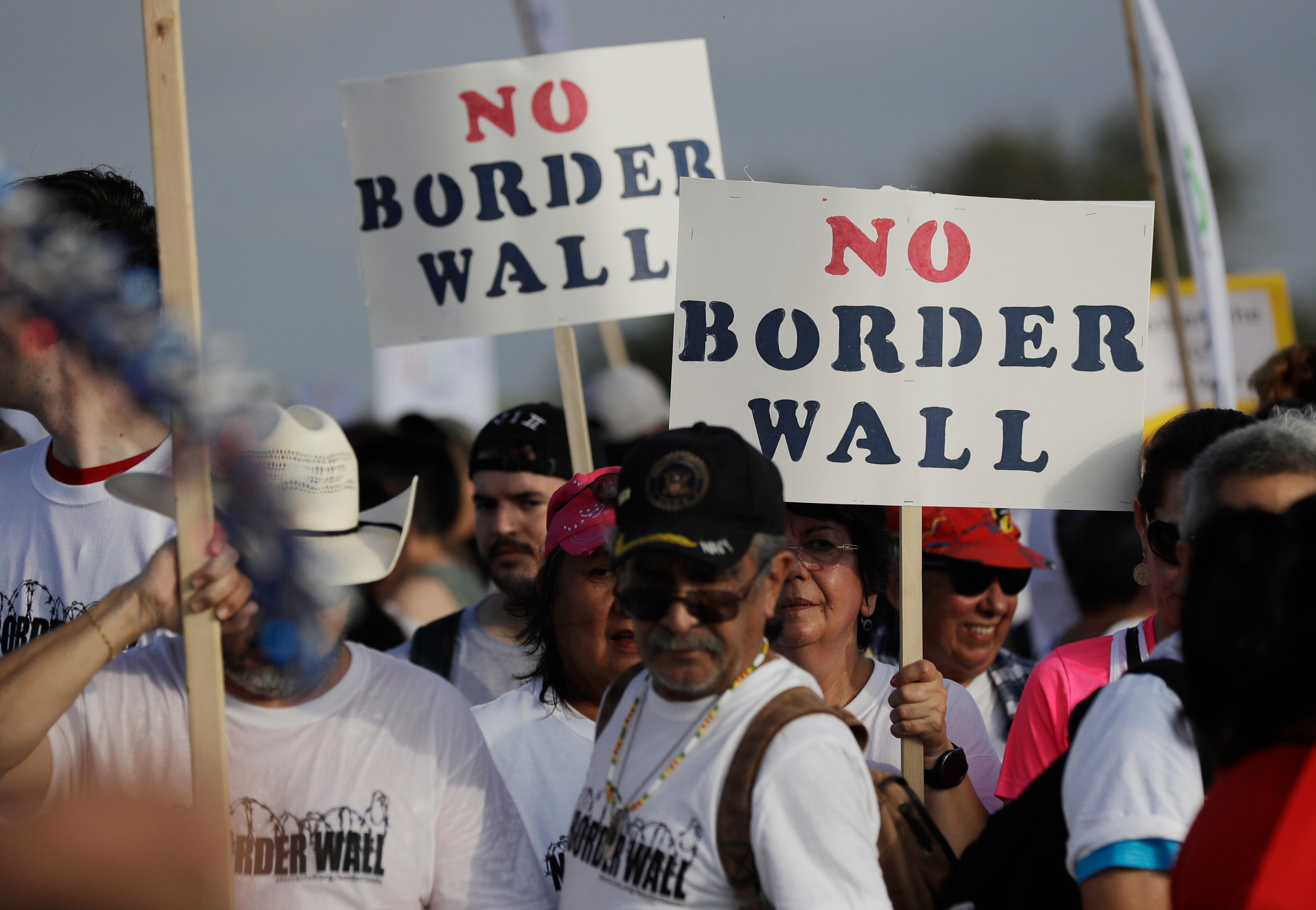 Hundreds of people march along a levee toward the Rio Grande to oppose the wall the U.S. government wants to build on the river separating Texas and Mexico, Saturday, Aug. 12, 2017, in Mission, Texas. The area would be the target of new barrier construction under the Trump administration's current plan. (AP Photo/Eric Gay)