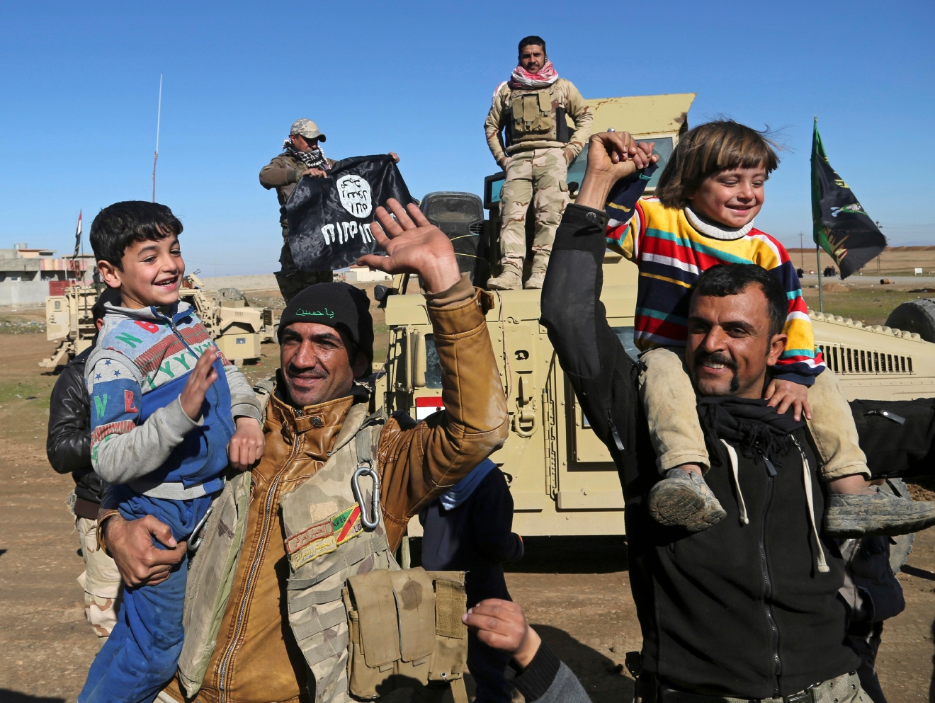Iraqi Army soldiers celebrate with residents of liberated neighborhoods as they hold upside down a flag of the Islamic State group, in the eastern side of Mosul, Iraq, Tuesday, Jan. 24, 2017. The U.N. and several aid organizations say an estimated 750,000 civilians are still living under Islamic State rule in Mosul despite recent advances by Iraqi forces. Lise Grande, the U.N. Humanitarian Coordinator for Iraq, said in a statement Tuesday that the cost of food and basic goods is soaring, water and electricity are intermittent and that some residents are forced to burn furniture to keep warm. (AP Photo/Khalid Mohammed)