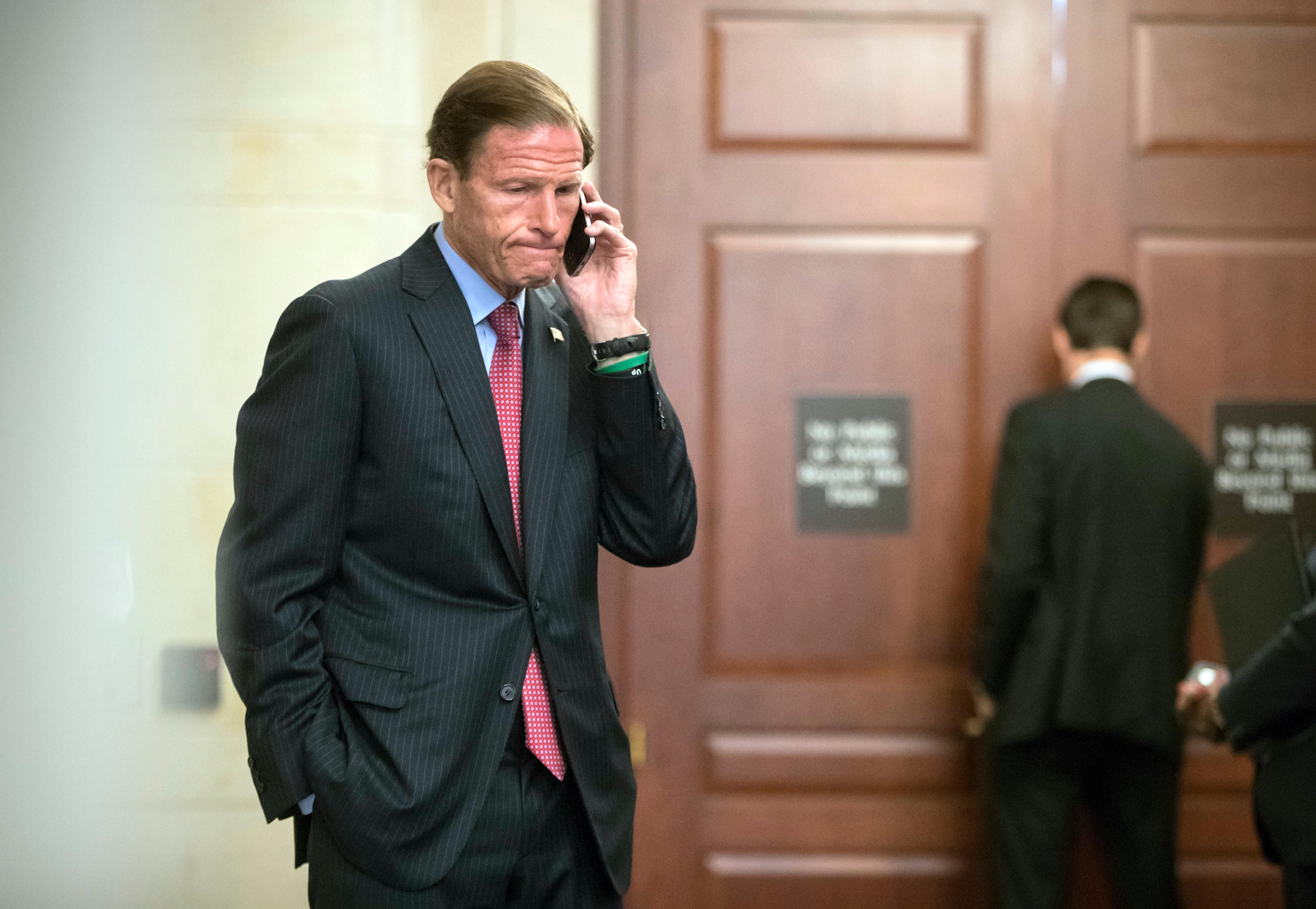 Sen. Richard Blumenthal, D-Conn., a member of the Senate Judiciary Committee, makes a phone call as Donald Trump Jr., interviewed behind closed doors by committee staff investigating the meddling and possible Russian links to President Donald Trump's 2016 presidential campaign, at the Capitol in Washington, Thursday, Sept. 7, 2017.  (AP Photo/J. Scott Applewhite)