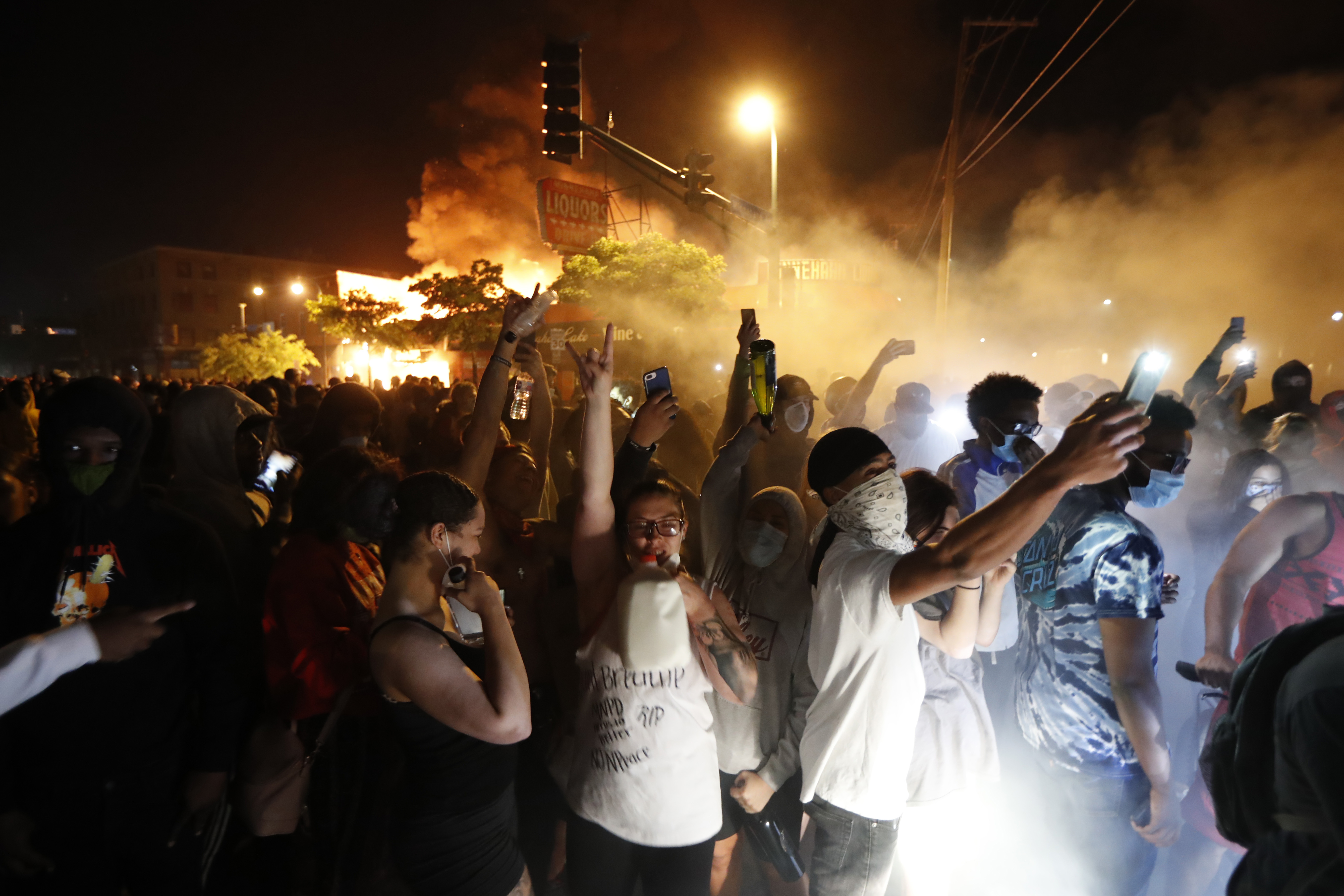 Protesters gather in front of the burning 3rd Precinct building of the Minneapolis Police Department on Thursday, May 28, 2020, in Minneapolis. (AP Photo/John Minchillo)