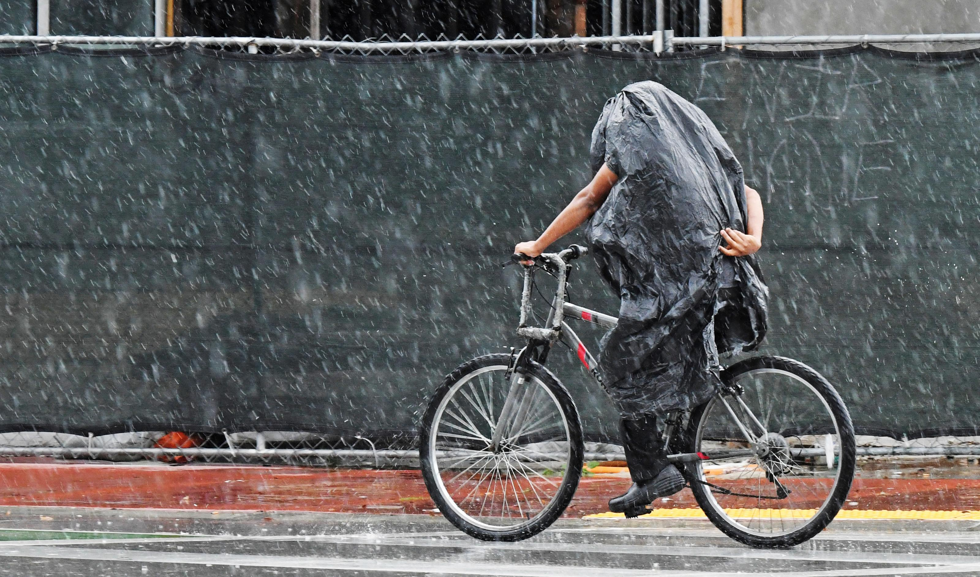 A cyclist tries to stay dry along Collins Ave. in Miami Beach, Fla., Friday, May 25, 2018. Rain from Subtropical Storm Alberto is expected to will drench the Memorial Day weekend. (Jim Rassol /South Florida Sun-Sentinel via AP)