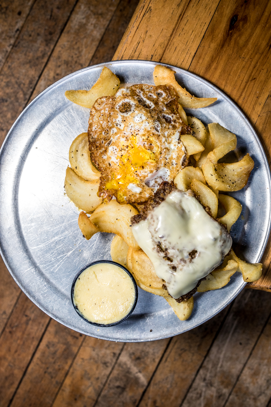 Cincy Fries with a slab of crispy goetta, american cheese, sriracha aioli, & an over easy egg paired with a red ale / Image: Catherine Viox{ }// Published: 3.12.20