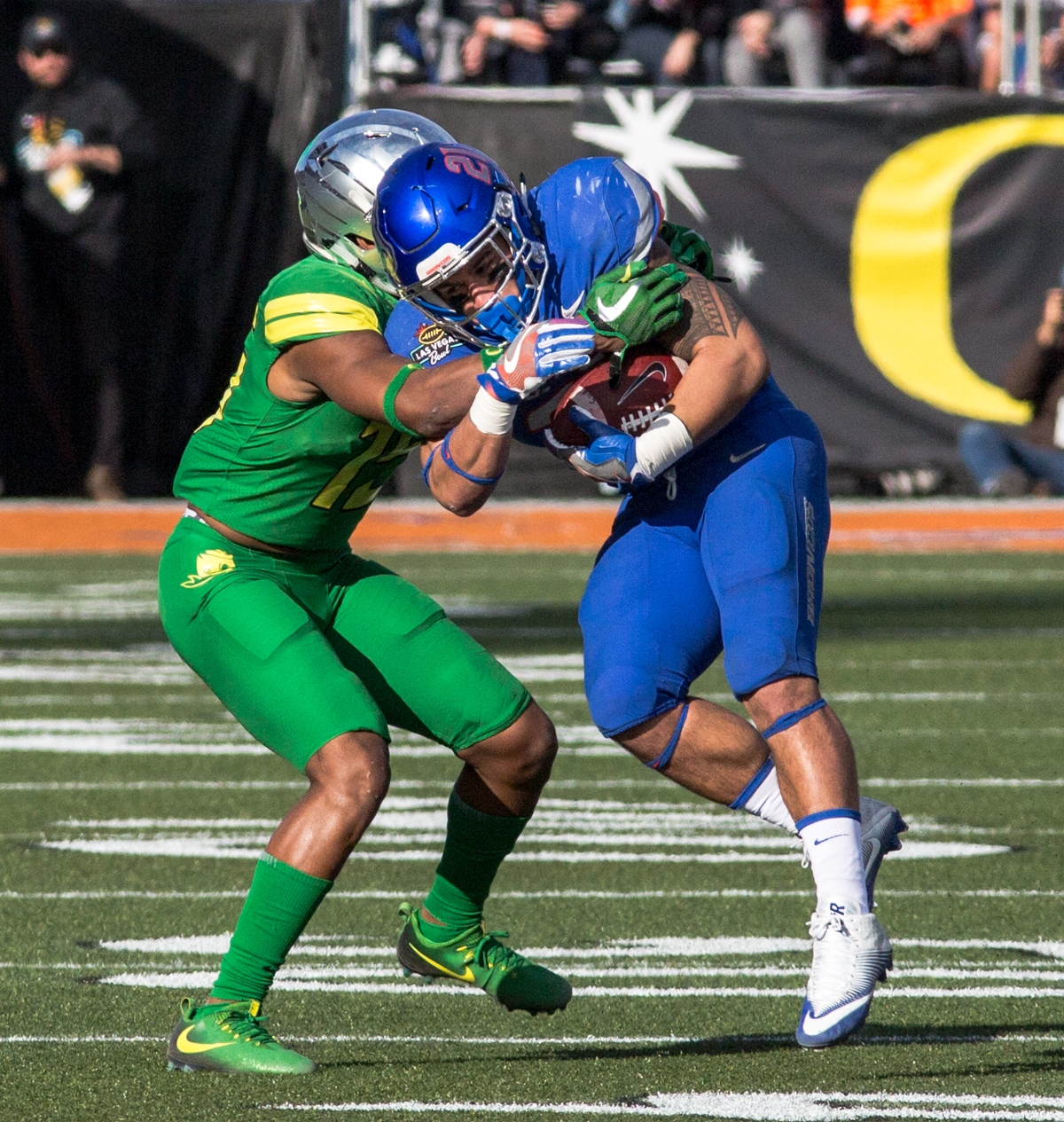 Boise State running back Ryan Wolpin (#21) tussles with an Oregon defender. The Boise State Broncos defeated the Oregon Ducks 38 to 28 in the 2017 Las Vegas Bowl at Sam Boyd Stadium in Las Vegas, Nevada on Saturday December 17, 2017. The Las Vegas Bowl served as the first test for Oregon's new Head Coach Mario Cristobal following the loss of former Head Coach Willie Taggart to Florida State University earlier this month. Photo by Ben Lonergan, Oregon News Lab