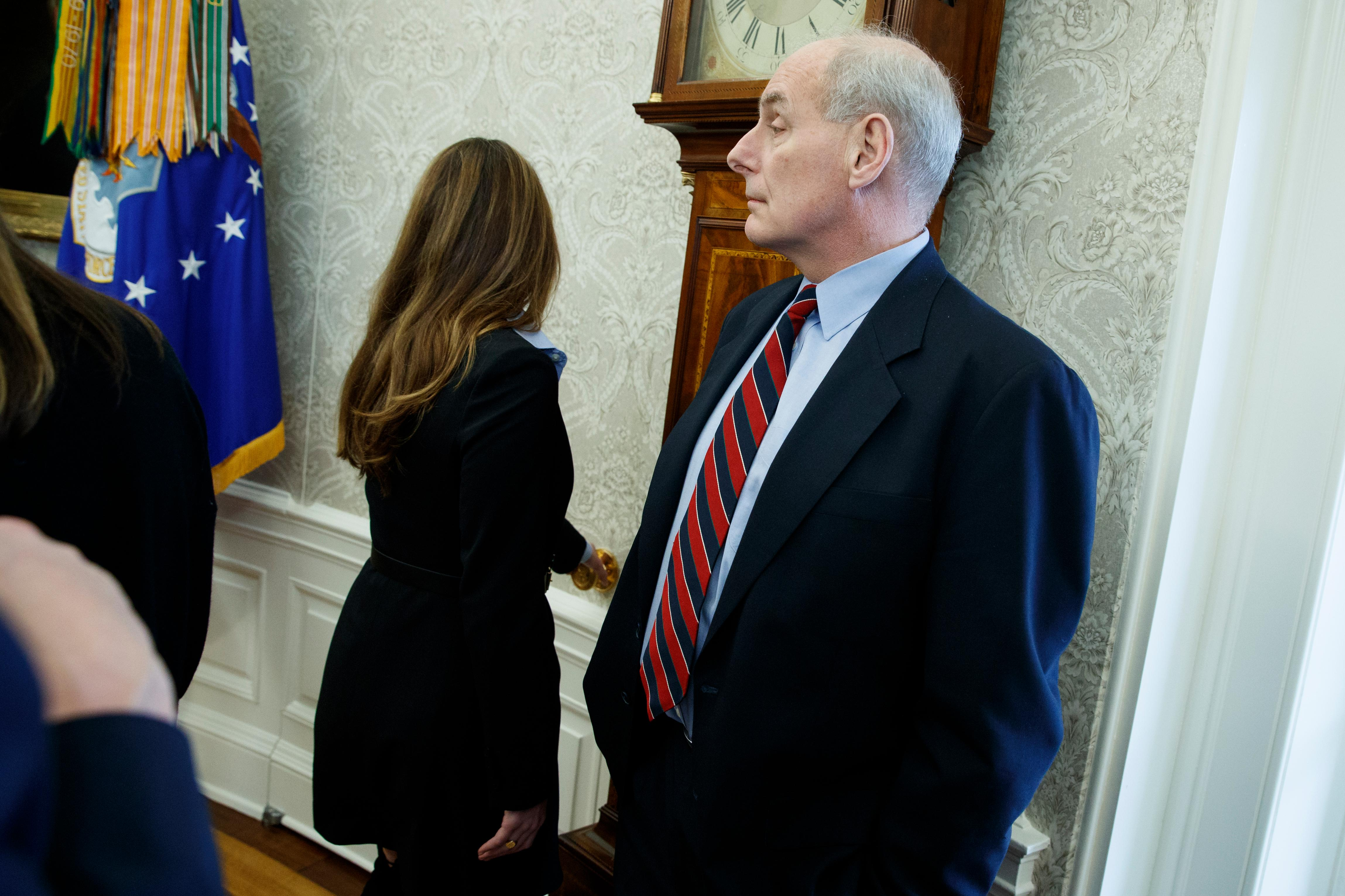 White House Communications Director Hope Hicks, left, walks out of the Oval Office as White House Chief of Staff John Kelly listens during a meeting between President Donald Trump and campaign volunteer Shane Bouvet, Friday, Feb. 9, 2018, in Washington. (AP Photo/Evan Vucci)