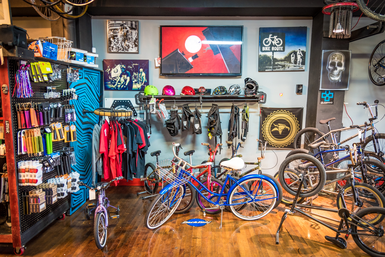Helmets and other apparel items are tucked neatly behind a row of BMX bikes. Cartoons play on a TV directly above them. / Image: Phil Armstrong, Cincinnati Refined // Published: 3.19.17