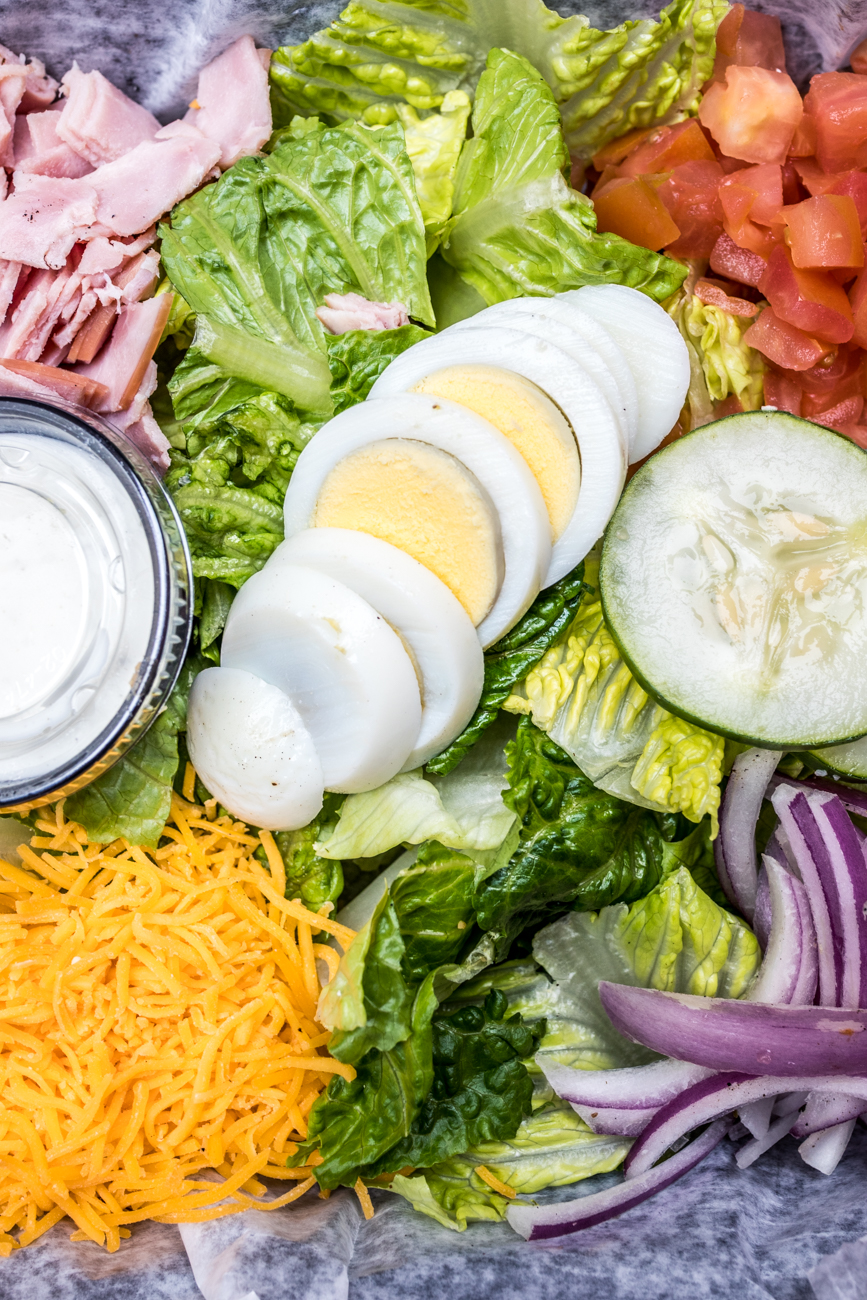 Chef salad: sliced ham, tomato, red onion, cucumber, cheddar cheese, and a hard boiled egg atop a bed of romaine / Image: Catherine Viox{ }// Published: 4.6.20