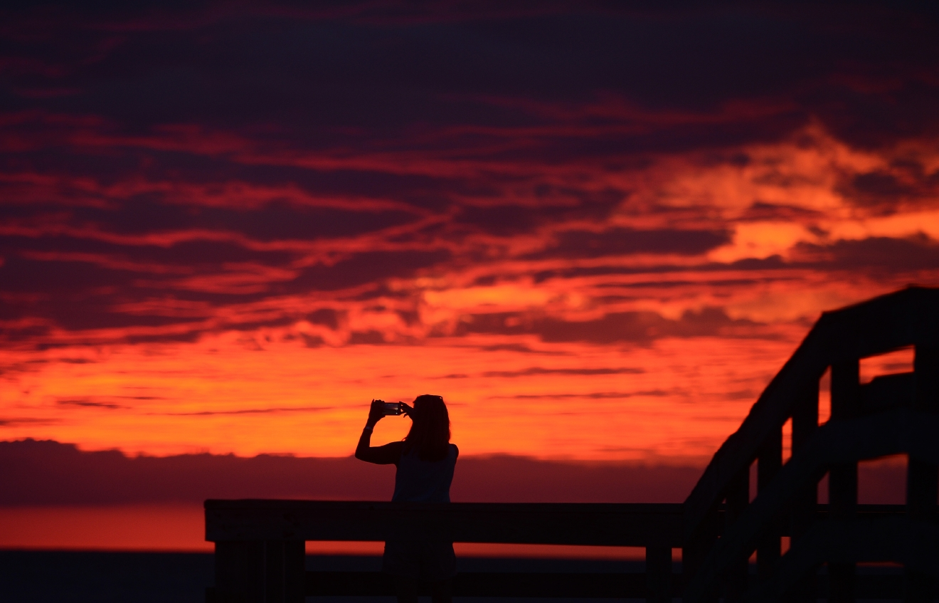 Karen Duer-Potts uses her cellphone to take a photograph of the sunset as the outer band of Hermine, which has weakened to a tropical storm, creeps over the beach at Cape Charles, Va., Friday, Sept. 2, 2016. (Jay Diem/The Daily Times via AP)