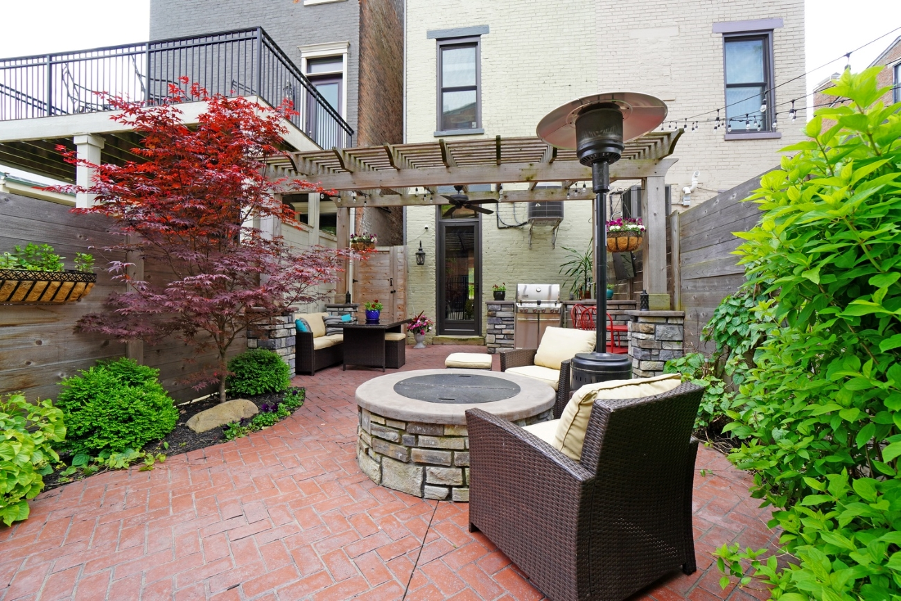 The home's outdoor space features a large custom-designed outdoor area with a built-in gas fire pit, grill, and Kegerator with tap. It also has a private rooftop deck that offers stunning views of downtown, Washington Park, and Music Hall. / Image courtesy of Brian Hubert via Comey & Shepherd{ }Realtors  // Published: 6.9.20