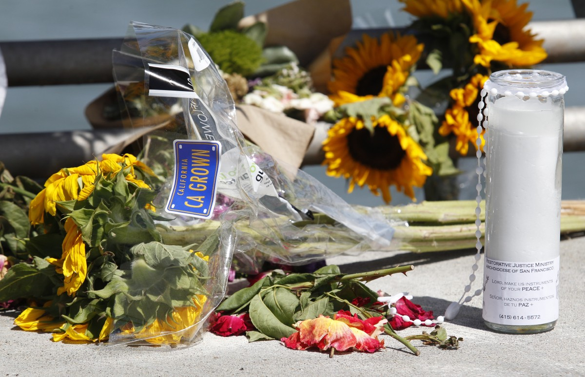 Flowers and a candle lay on the ground following a vigil for Kathryn Steinle, Monday, July 6, 2015, on Pier 14 in San Francisco. Steinle was gunned down while out for an evening stroll at Pier 14 with her father and a family friend on Wednesday, July 1. (AP Photo/Beck Diefenbach)