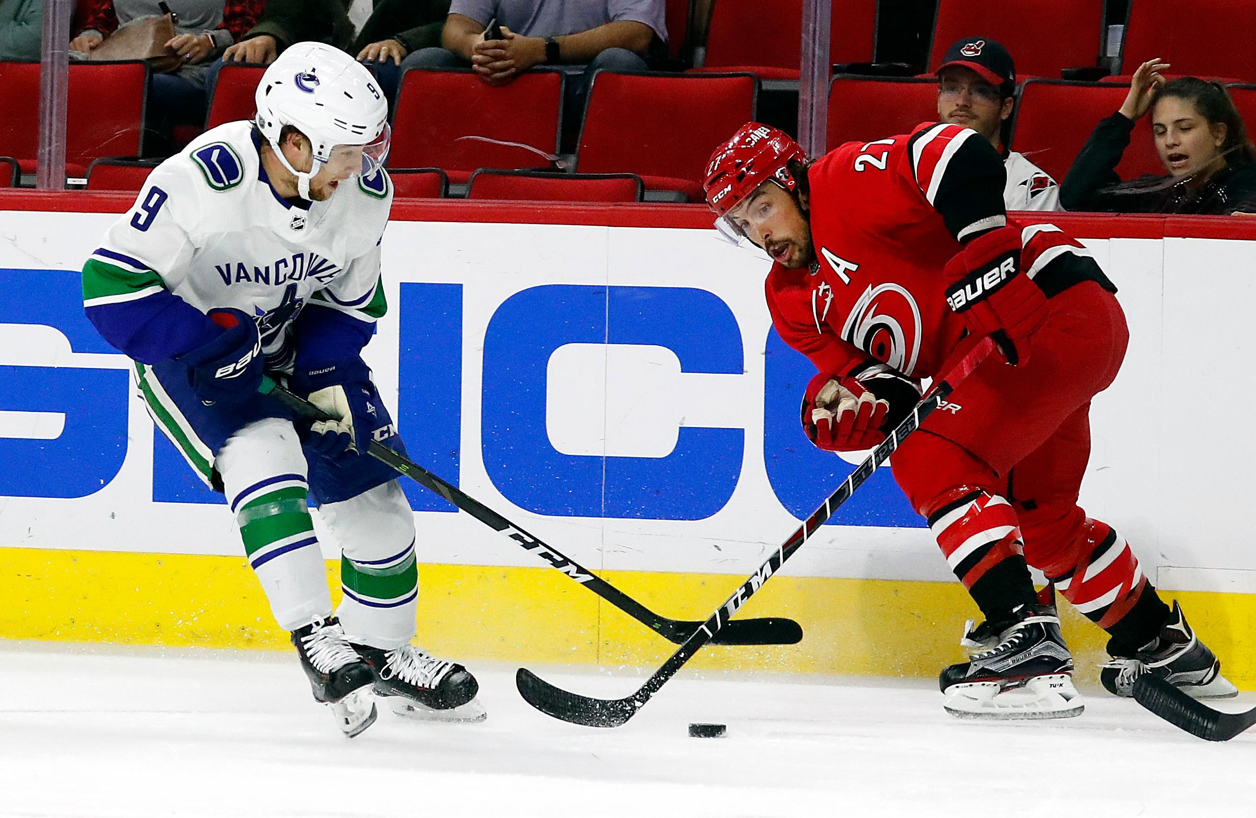 Carolina Hurricanes' Justin Faulk (27) battles with Vancouver Canucks' Brendan Leipsic (9) during the first period of an NHL hockey game, Tuesday, Oct. 9, 2018, in Raleigh, N.C. (AP Photo/Karl B DeBlaker)