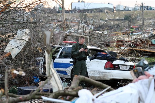 A police officer checks his phone while standing amid wreckage in Henryville, Ind., Friday.