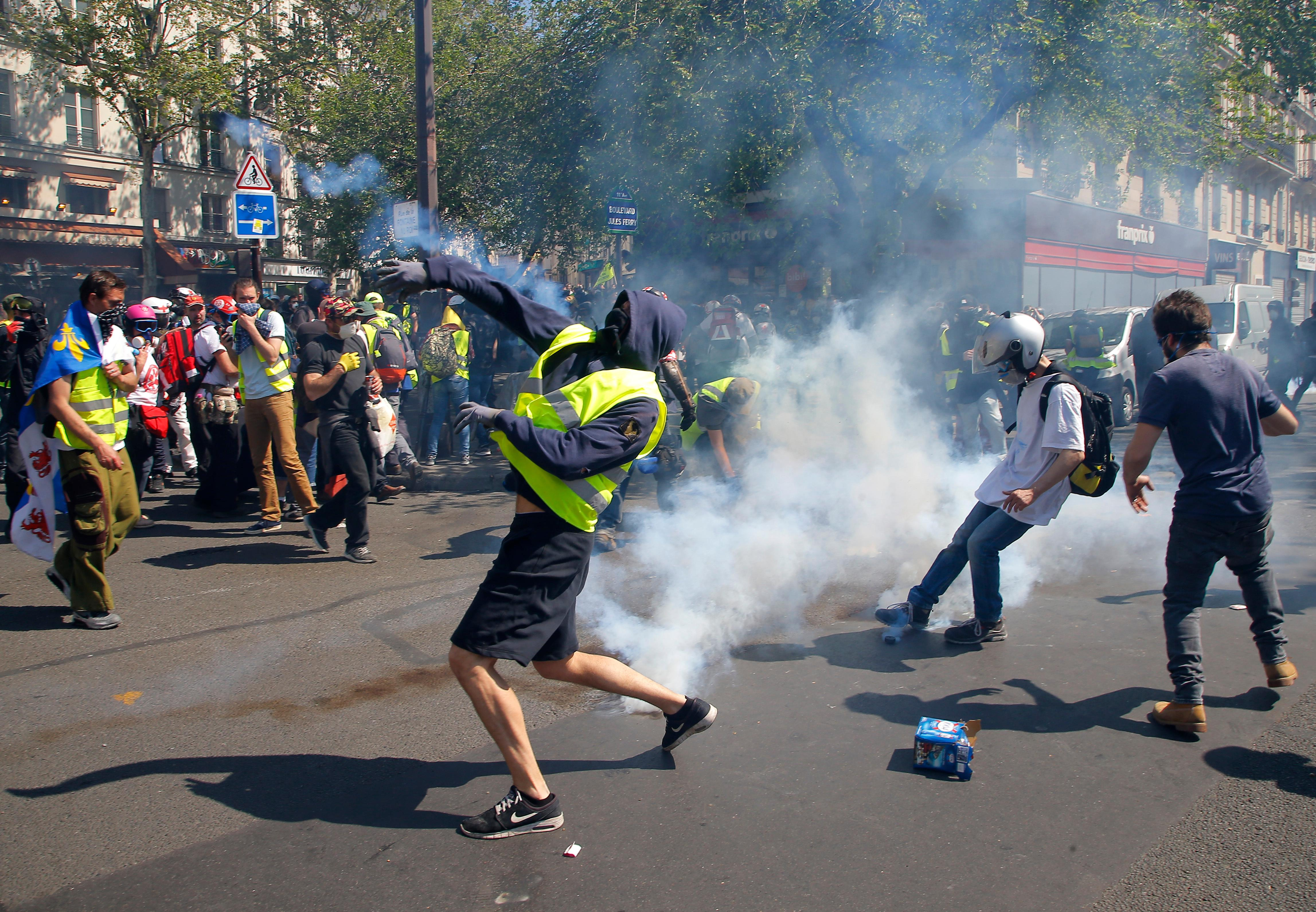 A demonstrator throws back a tear gas canister during a yellow vest demonstration in Paris, Saturday, April 20, 2019. French yellow vest protesters are marching anew to remind the government that rebuilding the fire-ravaged Notre Dame Cathedral isn't the only problem the nation needs to solve. (AP Photo/Michel Euler)