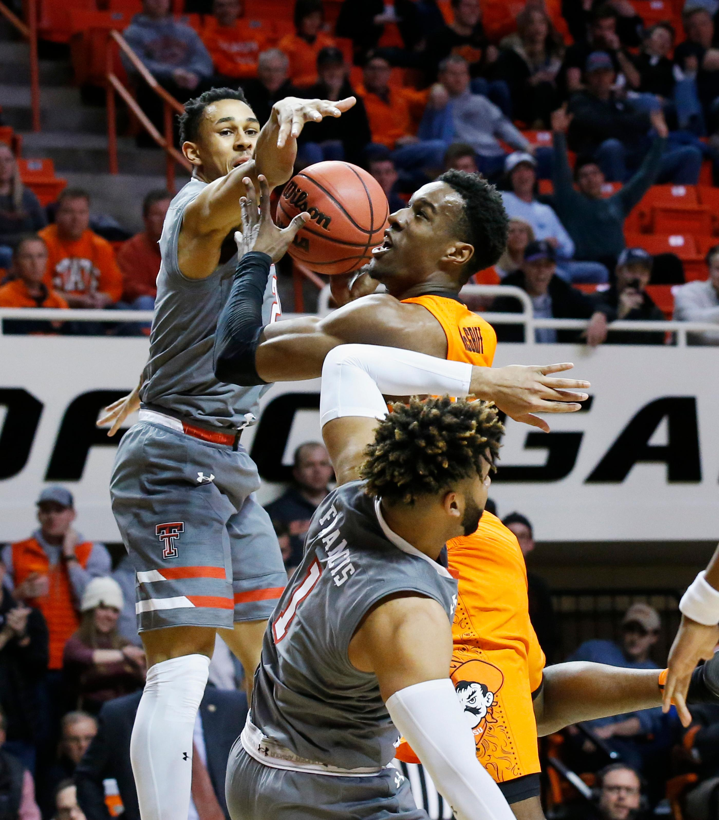 Oklahoma State forward Cameron McGriff, center, drives to the basket between Texas Tech guard Zhaire Smith, left, and guard Brandone Francis (1) during the first half of an NCAA college basketball game in Stillwater, Okla., Wednesday, Feb. 21, 2018. (AP Photo/Sue Ogrocki)