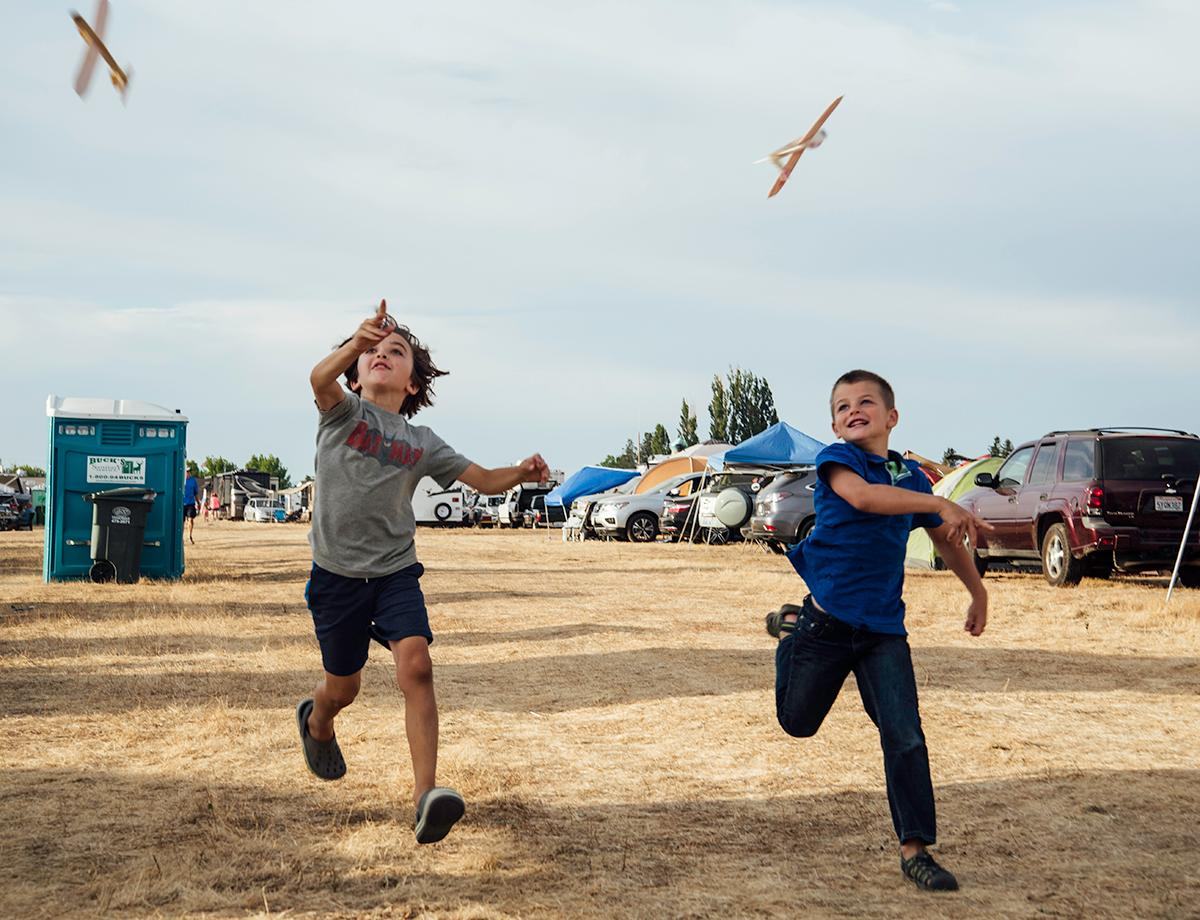 Parker Milam and Kaiden Lang brought their own toy airplanes to race and fly as a source of entertainment before the eclipse at the Solar Port campgrounds at the Madras Airport. Photo by Cheyenne Thorpe, Oregon News Lab
