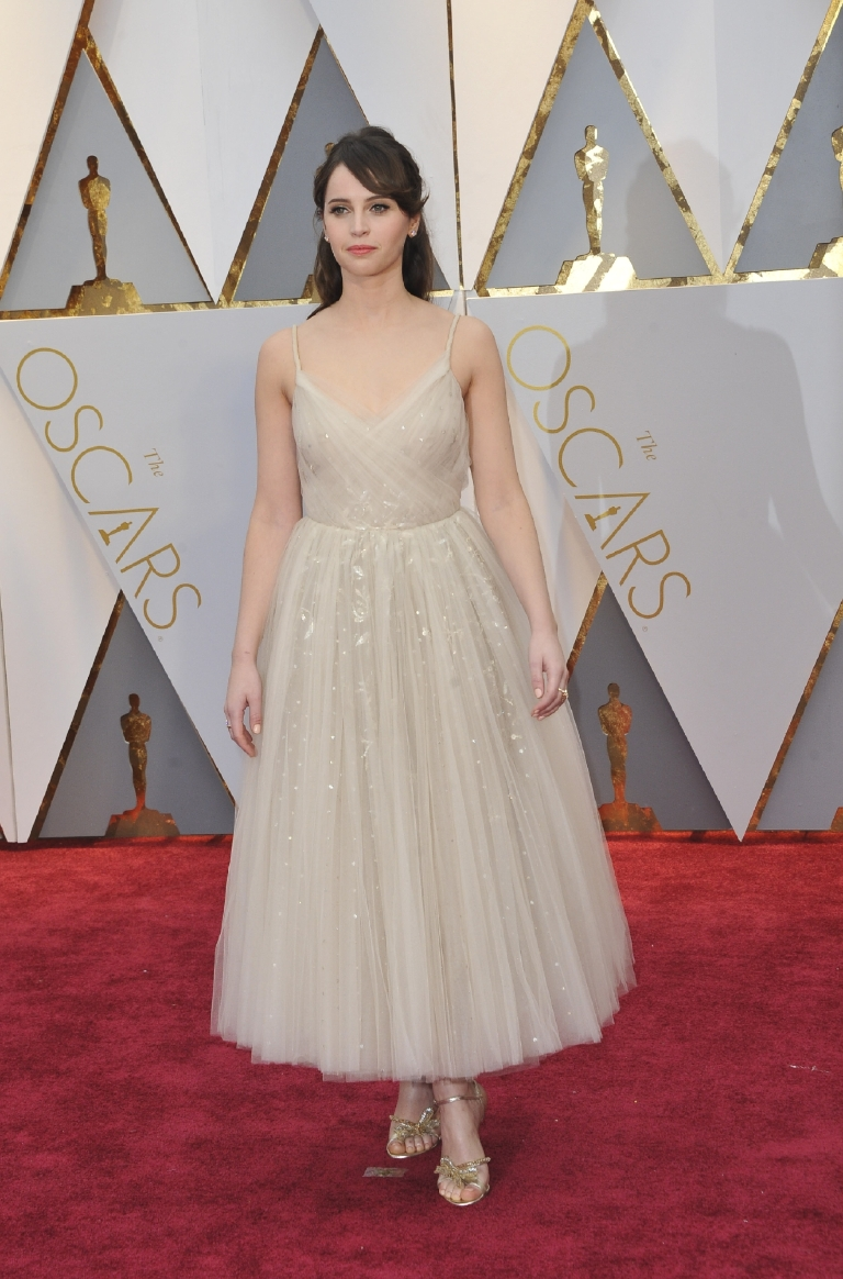 Felicity, darling, it's time to get a second opinion on your fashion choices. Between the pink tulle monstrosity with the odd bow from the Golden Globes to this nude, teacup gown that looks somewhat reminiscent of a ballerina's tutu gone rogue, she just can't hit the mark. (Image: Apega/WENN.com)