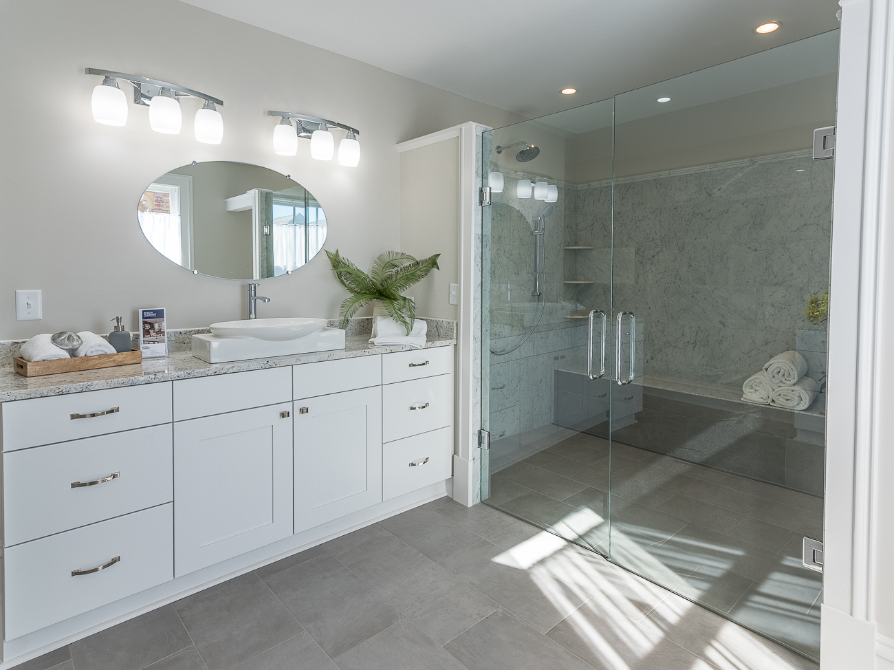 In the event you need to fit 11 people into a single shower, the master bedroom suite has one with double glass doors, two shower heads, and a built-in bench. Two full vanities are situated on either wall. / Image: Phil Armstrong, Cincinnati Refined // Published: 10.22.17<p></p>