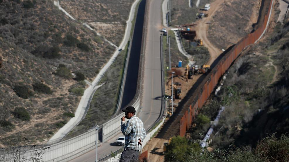 a man looks out at the us border where workers are replacing parts of the us border wall for a higher one in tijuana mexico wednesday dec 19 2018