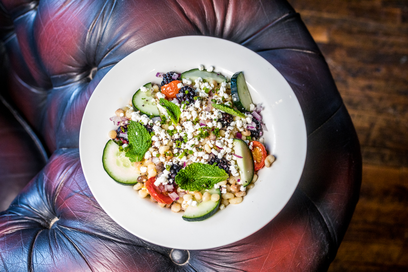 Fregola Salad: roasted cherry tomatoes, cucumber, onion, fresh blackberries, mint, and crumbled goat cheese topped with an orange green tea vinaigrette / Image: Catherine Viox{ }// Published: 7.16.20